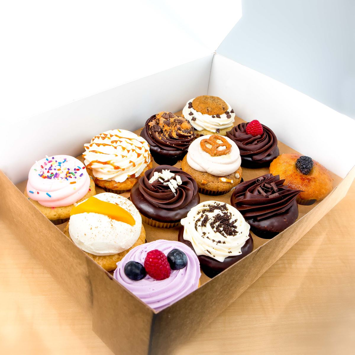 A box holds 12 cupcakes decorated with pink, white, chocolate, and orange frosting.