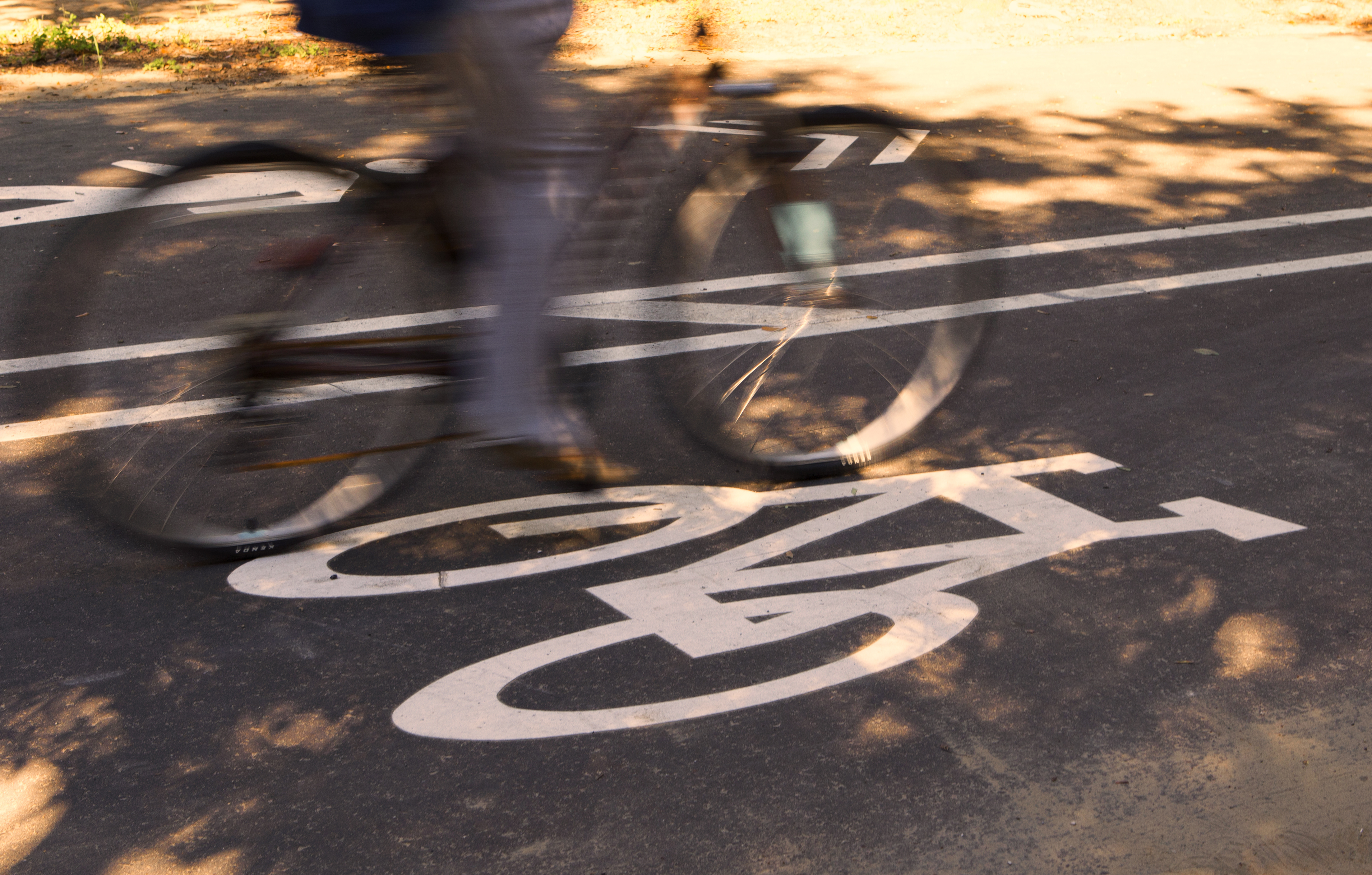 A bicycle is captured in a blur as it speeds over a white bike lane sign on a concrete road.