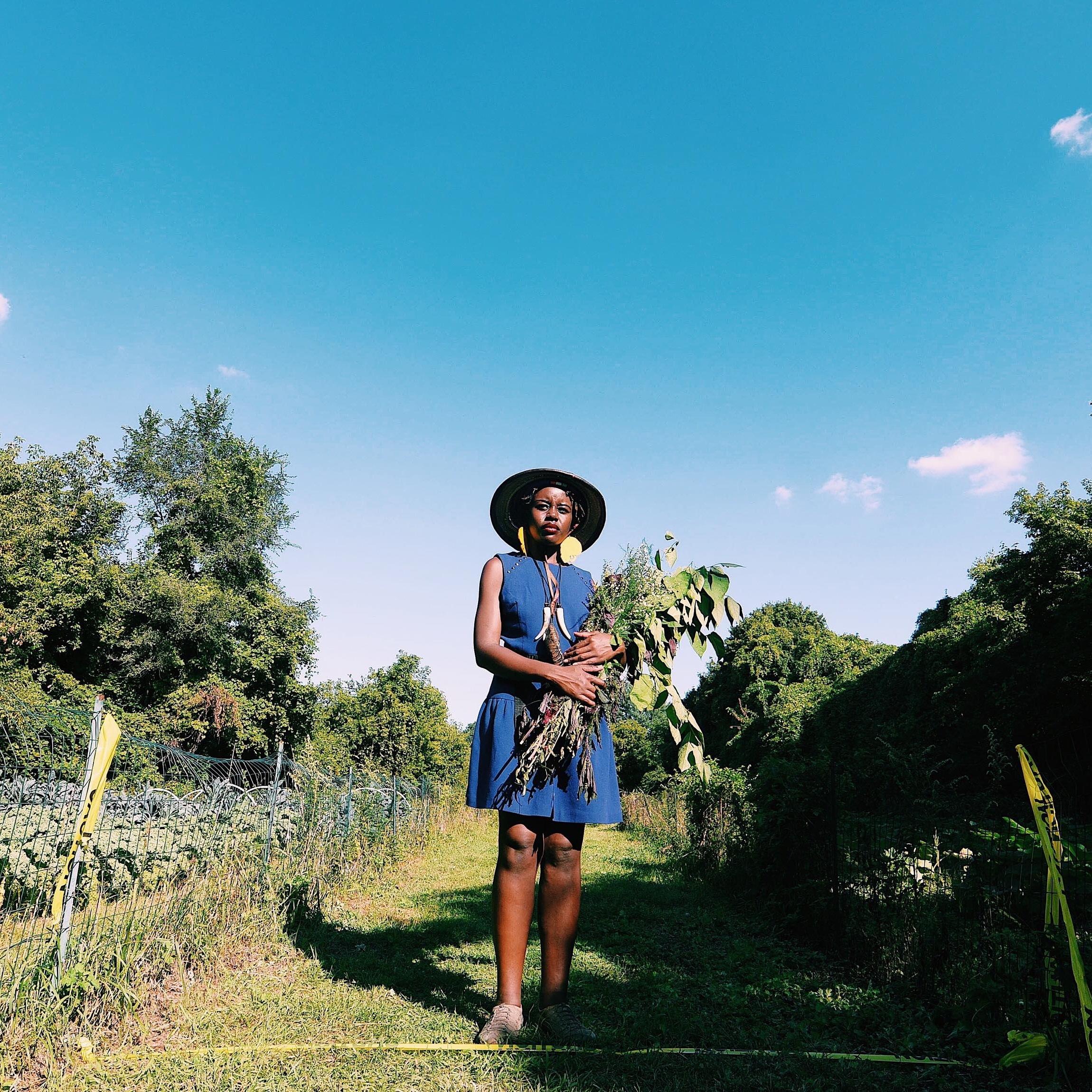 Farmer Atieno Kasagam holds produce in an urban farm in Detroit