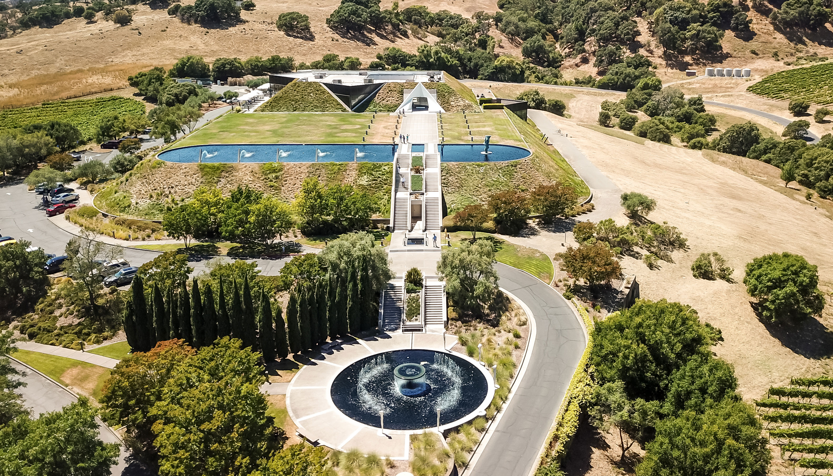 An aerial view of a winery with trees, a fountain, vineyards and rolling hills.