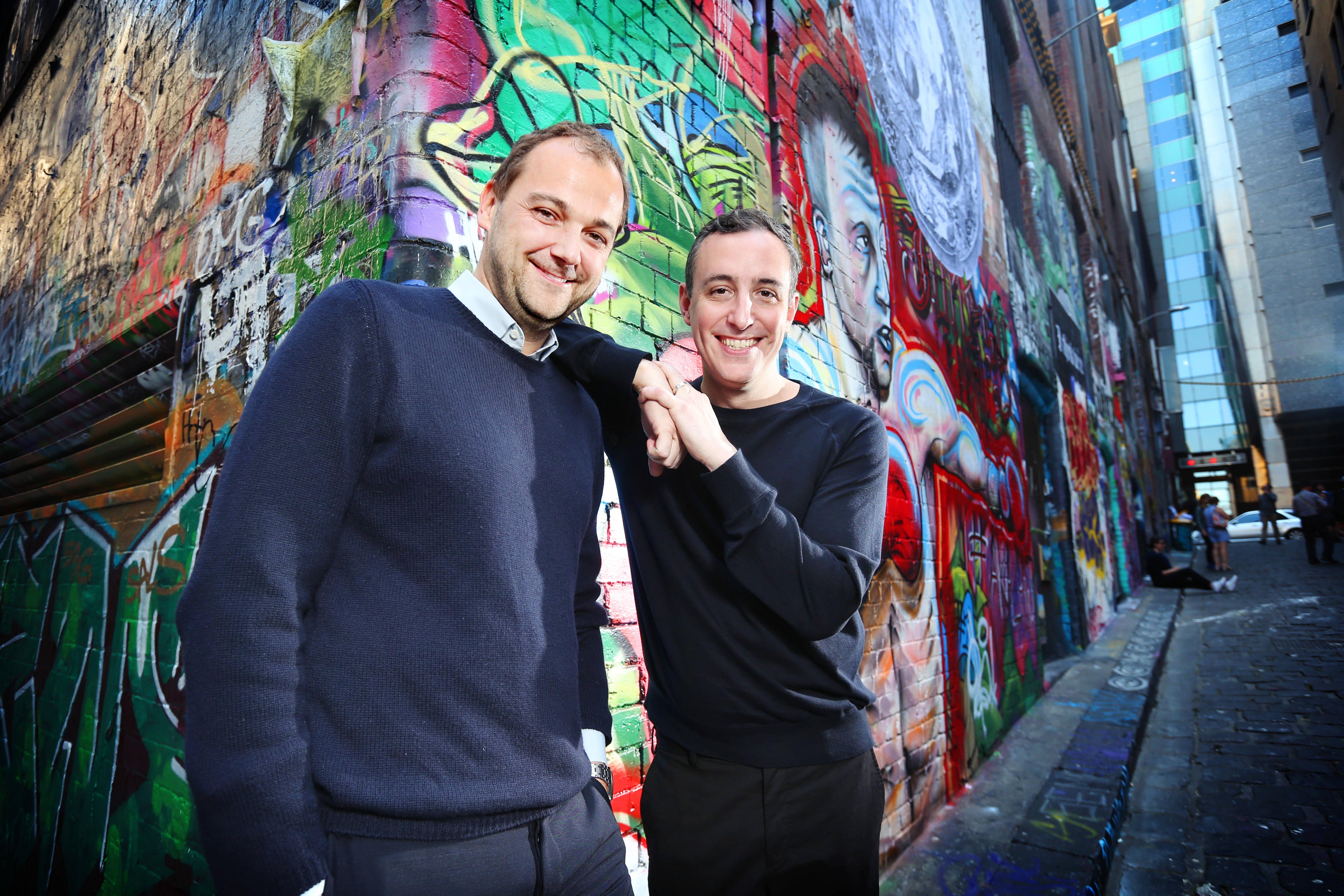 Daniel Humm & Will Guidara post in front of graffiti during a photo shoot