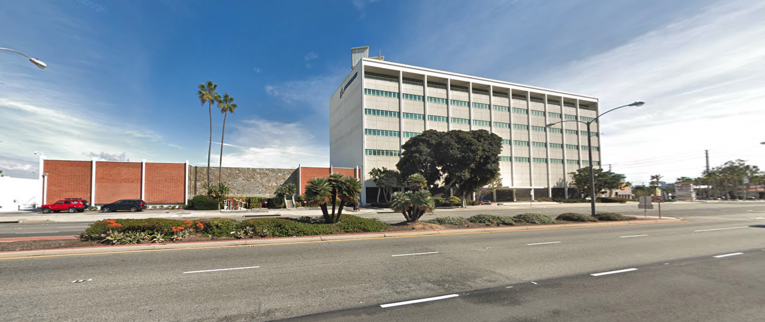 A street view of the two-story and eight-story buildings included in the sale, as seen from PCH.