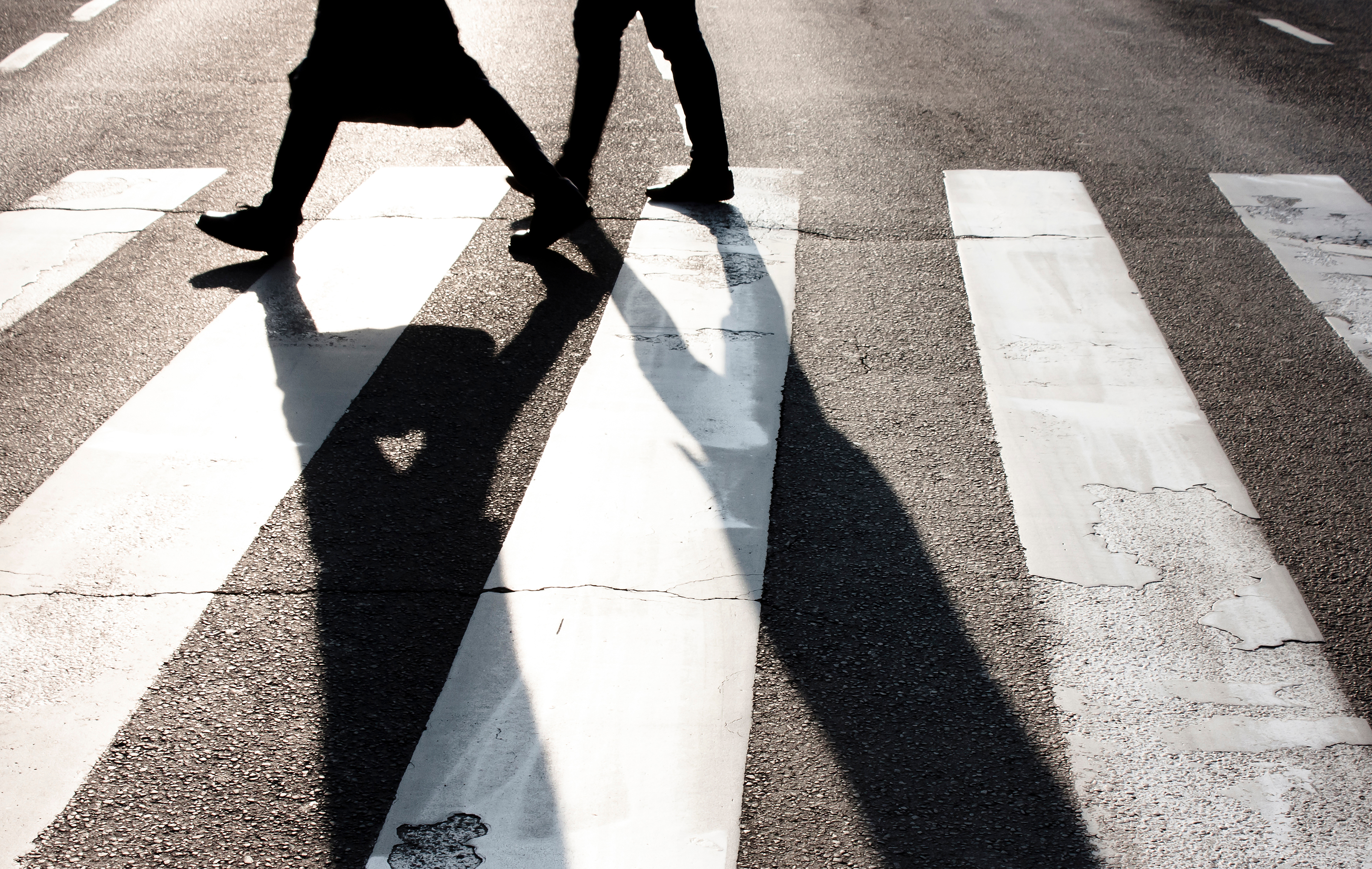 The legs of two pedestrians and their shadows are seen traversing a zebra crosswalk.