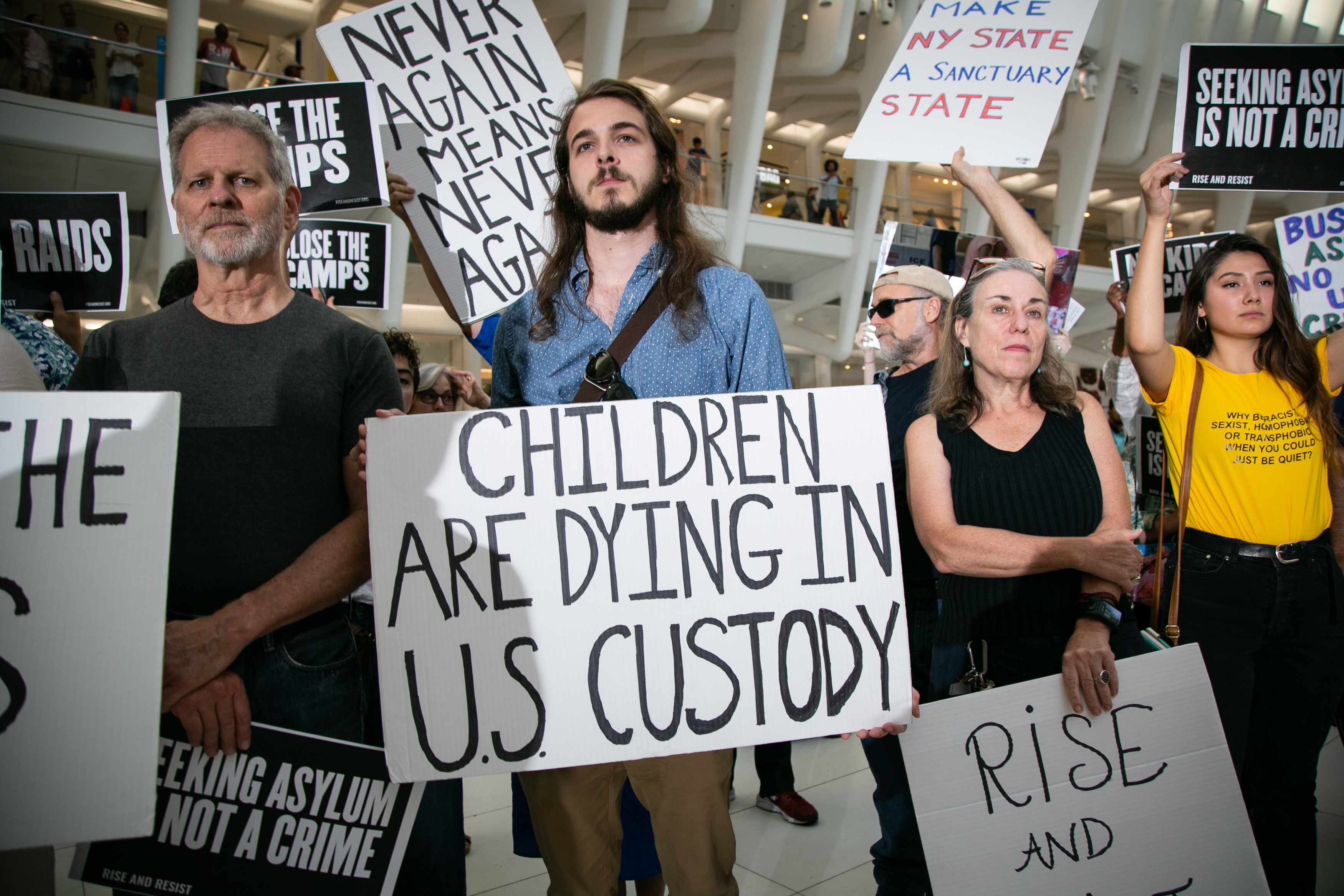 "People in New York City hold up signs protesting Immigration and Customs Enforcement. The main sign reads, ""Children are dying in US custody."""