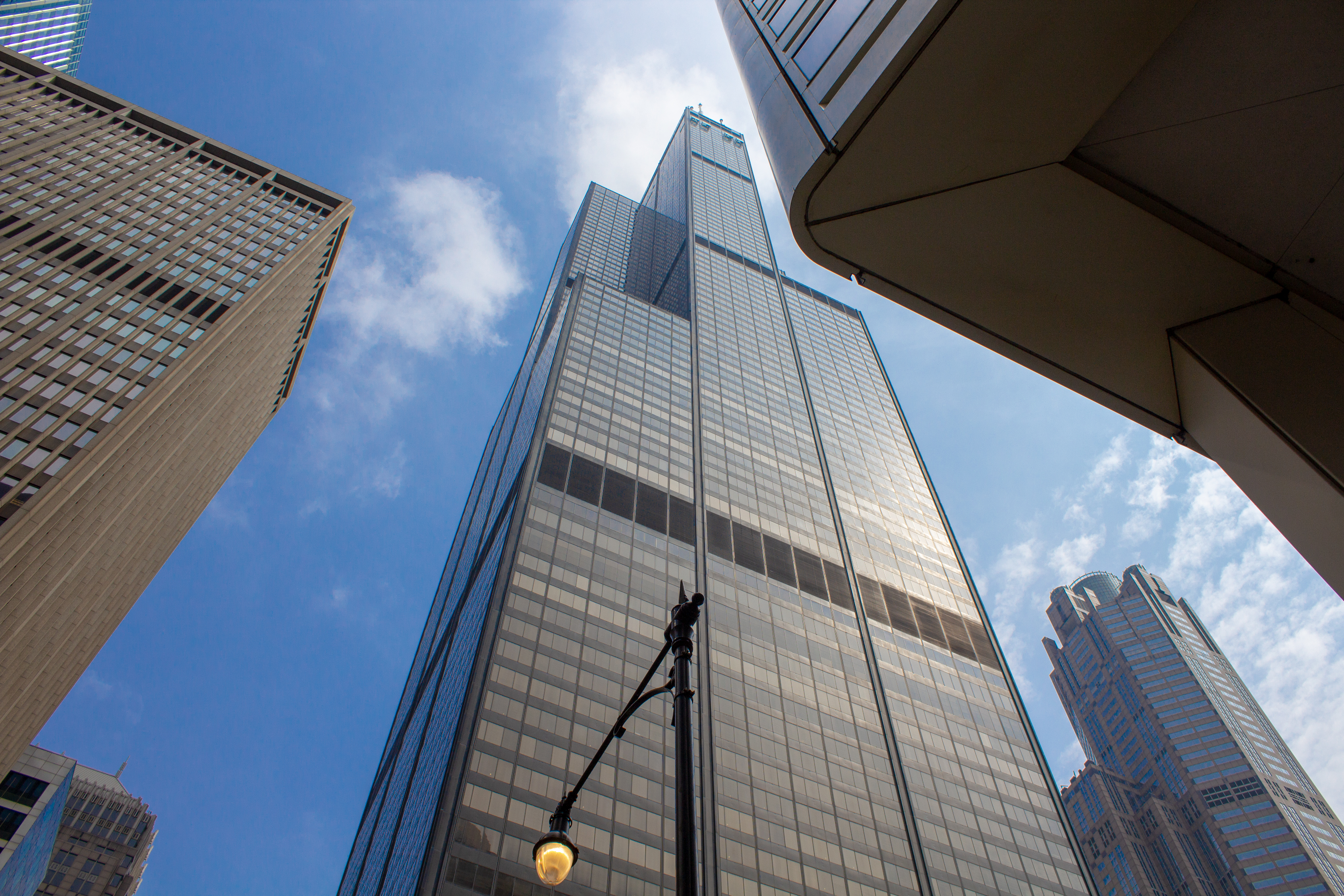 A street-level view of a tall, black skyscraper with offset setbacks that tapers under a blue and cloudy sky.