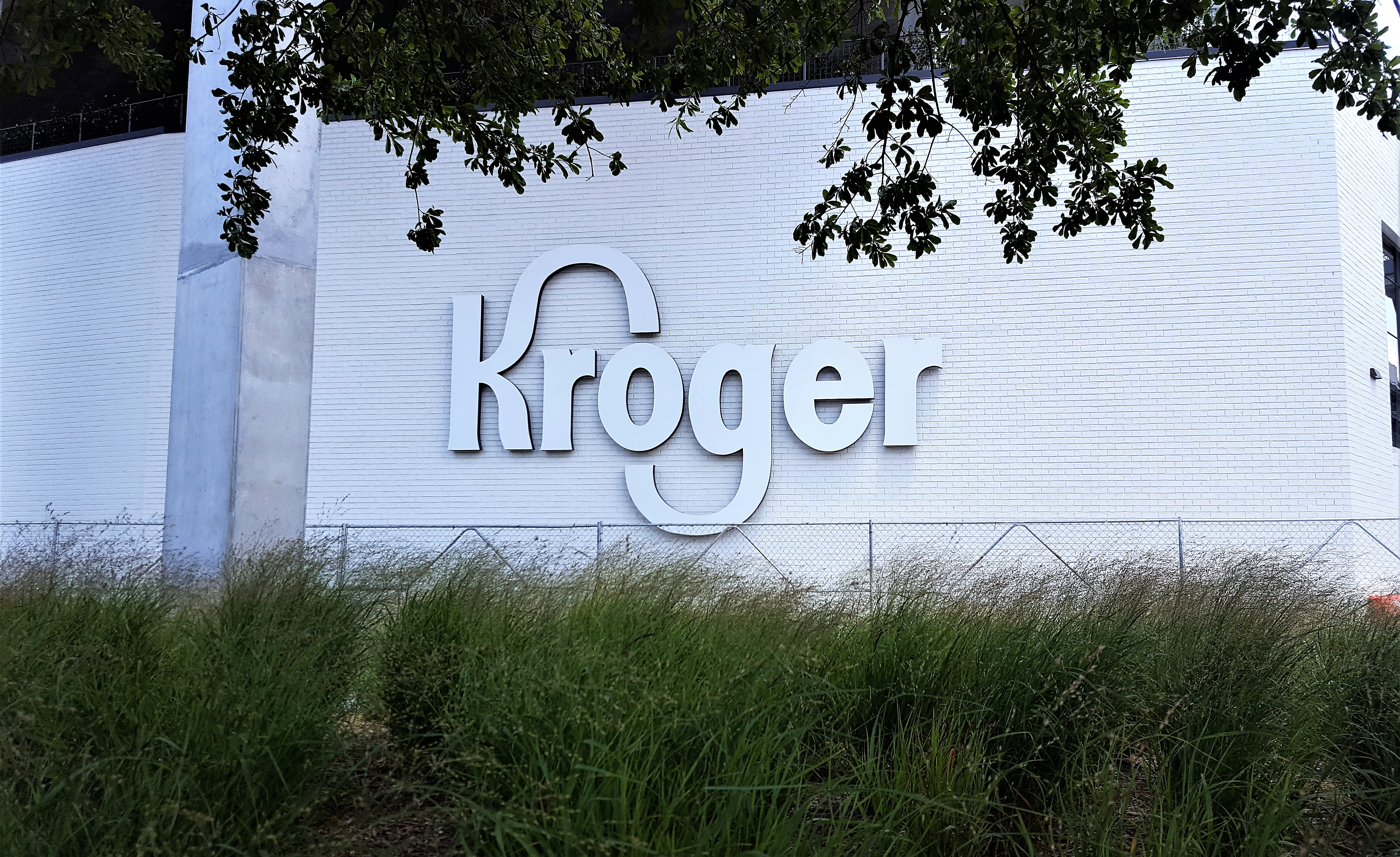 A picture of a new white Kroger logo hung on a white brick wall in front of the Beltline.