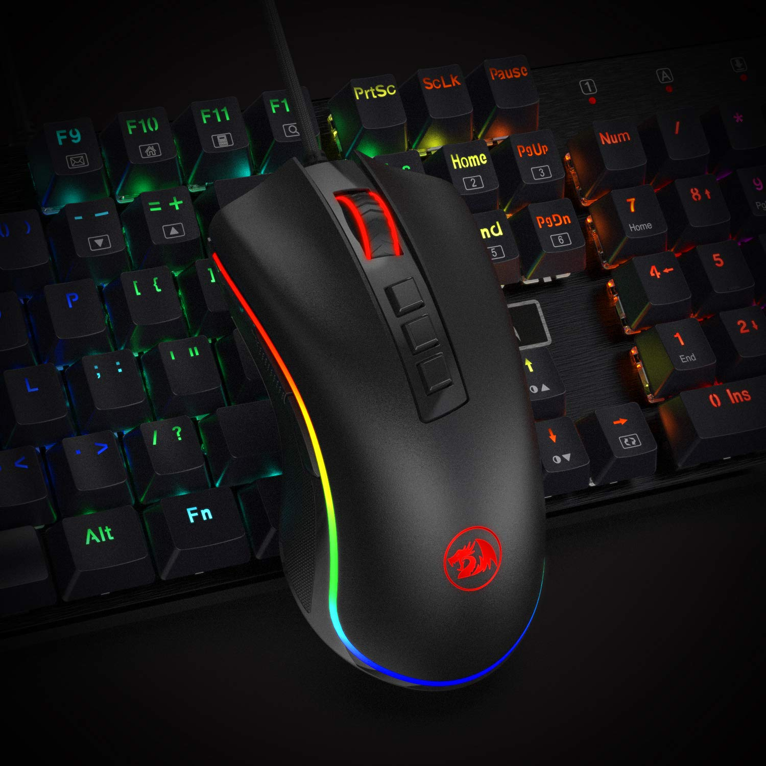 A rainbow-backlit gaming keyboard with a mouse lying on top of it