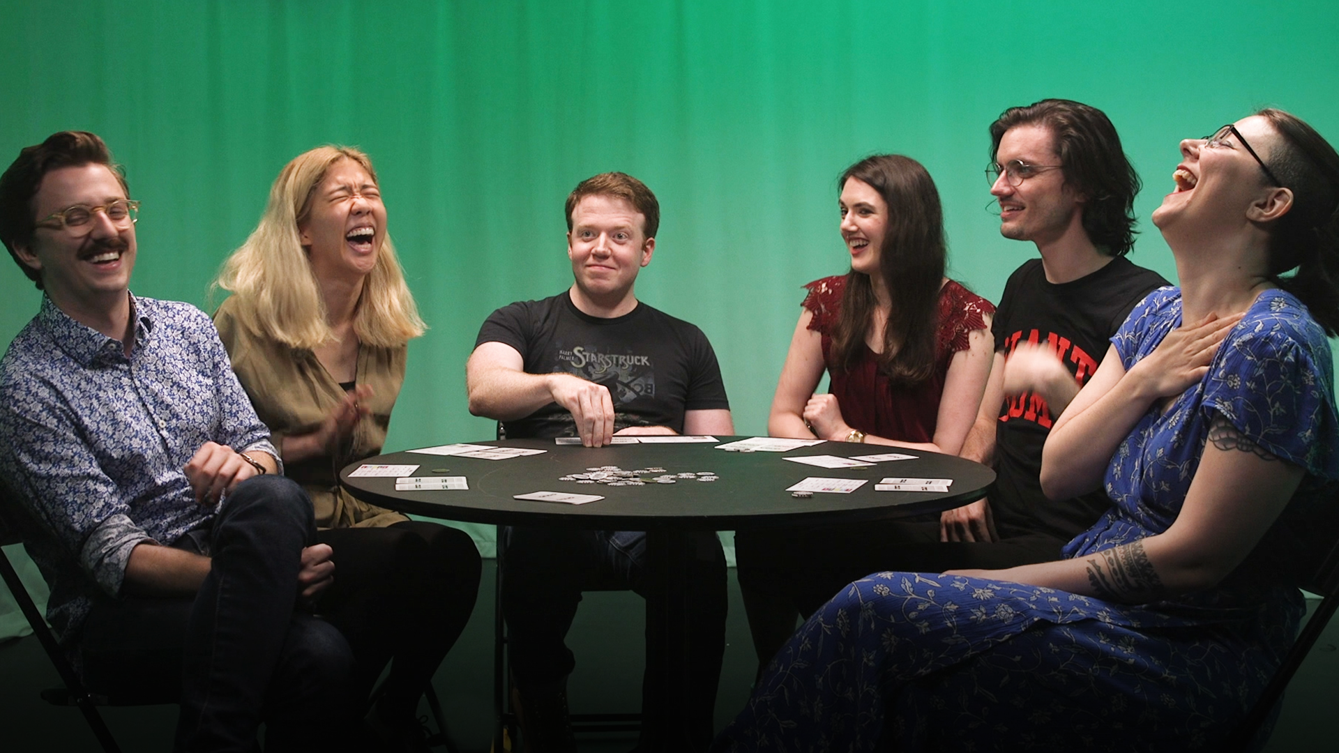 A group of friends laughs while playing the board game Coup.