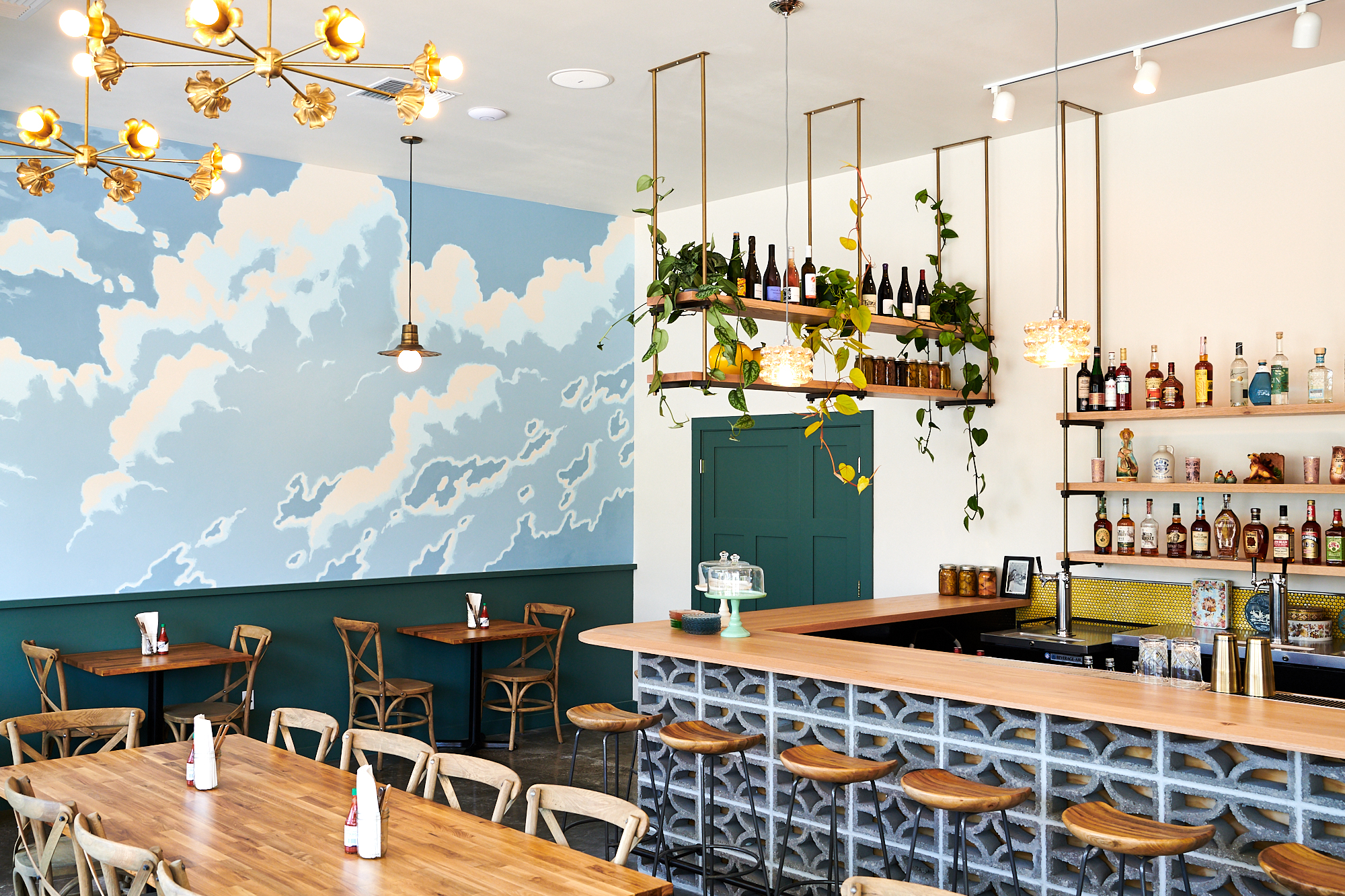 A picture of the blue interiors of Yonder, with wooden stools lining up at a bar