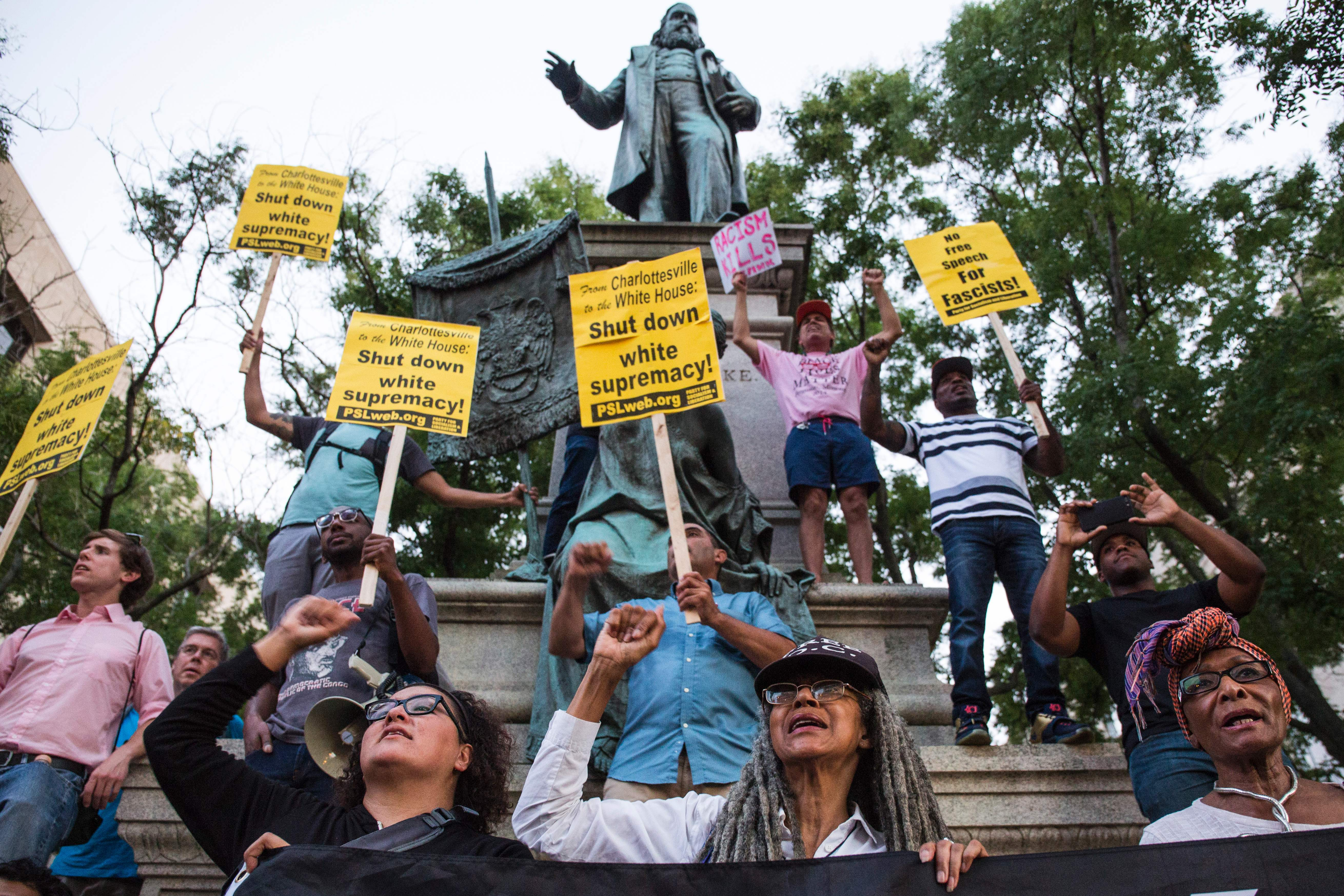 """Several protesters demonstrate at the Albert Pike statue on August 13, 2017. Some of the protesters hold yellow signs that in part say """"shut down white supremacy."""" The statue is seen above them."""