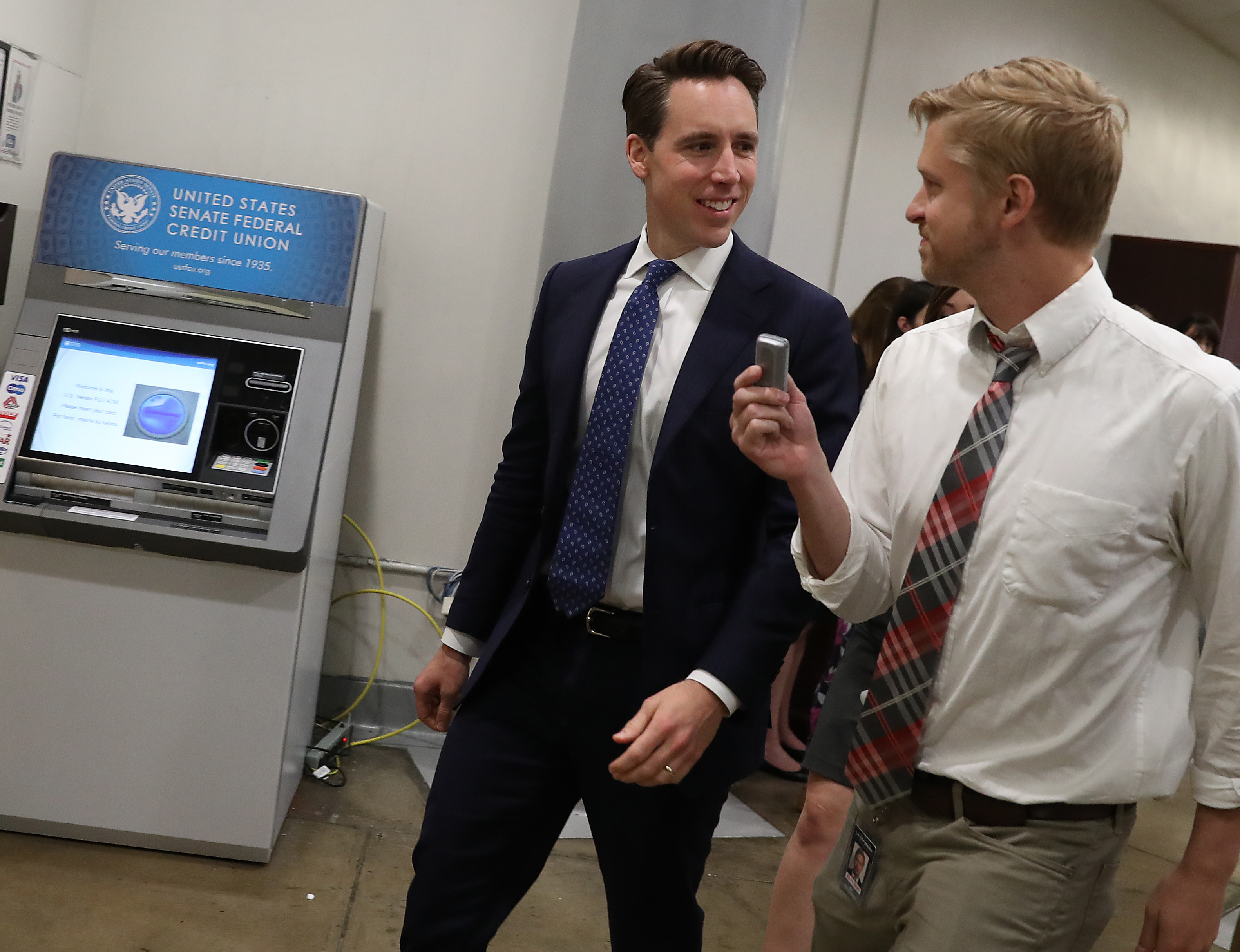 Senator Josh Hawley speaks to a reporter in a hallway.
