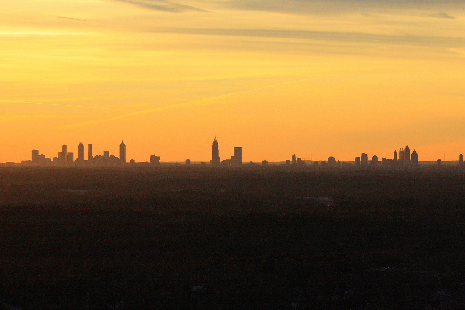 The skyline from Stone Mountain, with a yellow sunset topping a silhouette of the city.