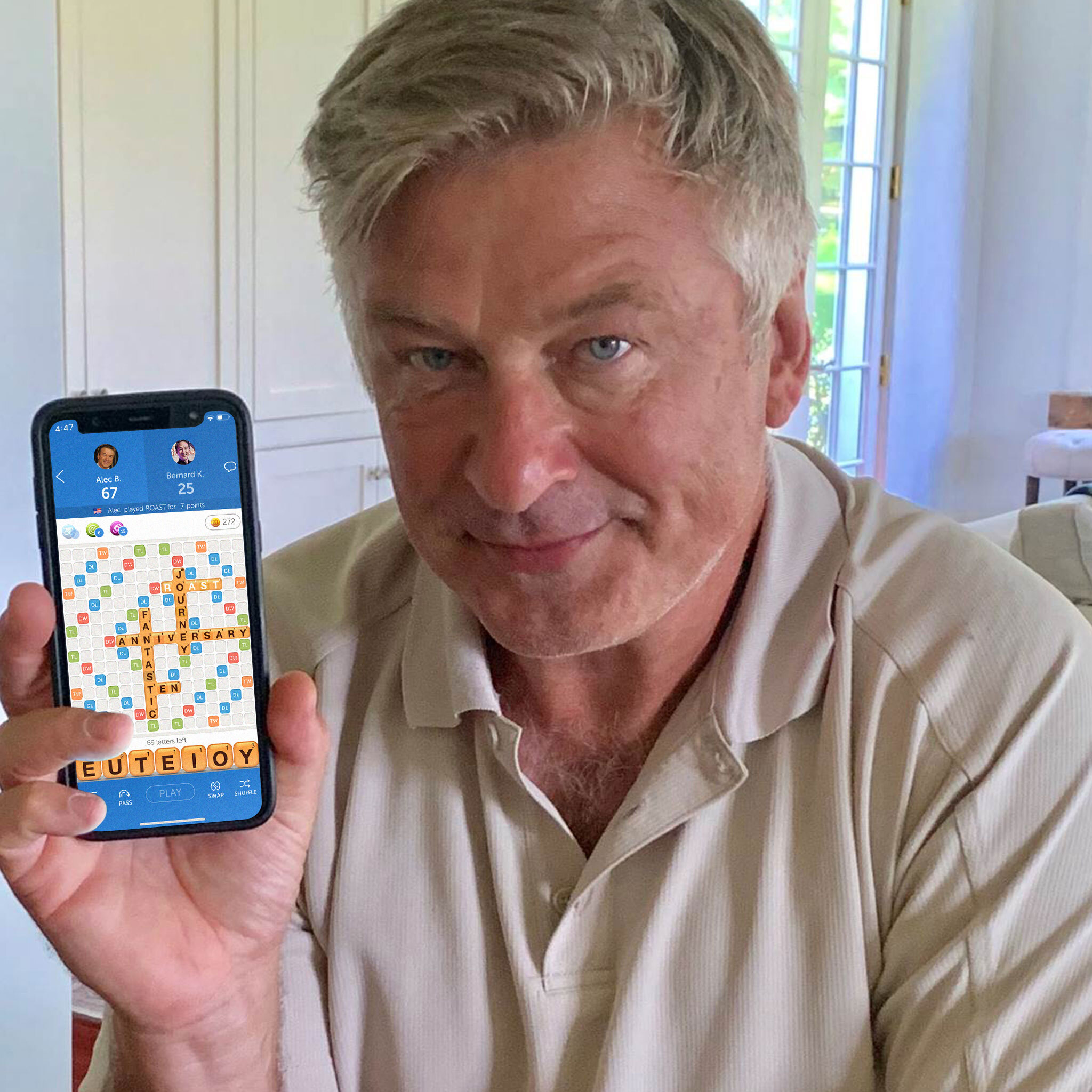 An aging man — Alec Baldwin— with gray hair and a tan polo shirt has a mostly neutral expression on his face. He is slightly smirking and holding up an iPhone with a game of Words With Friends on the screen.