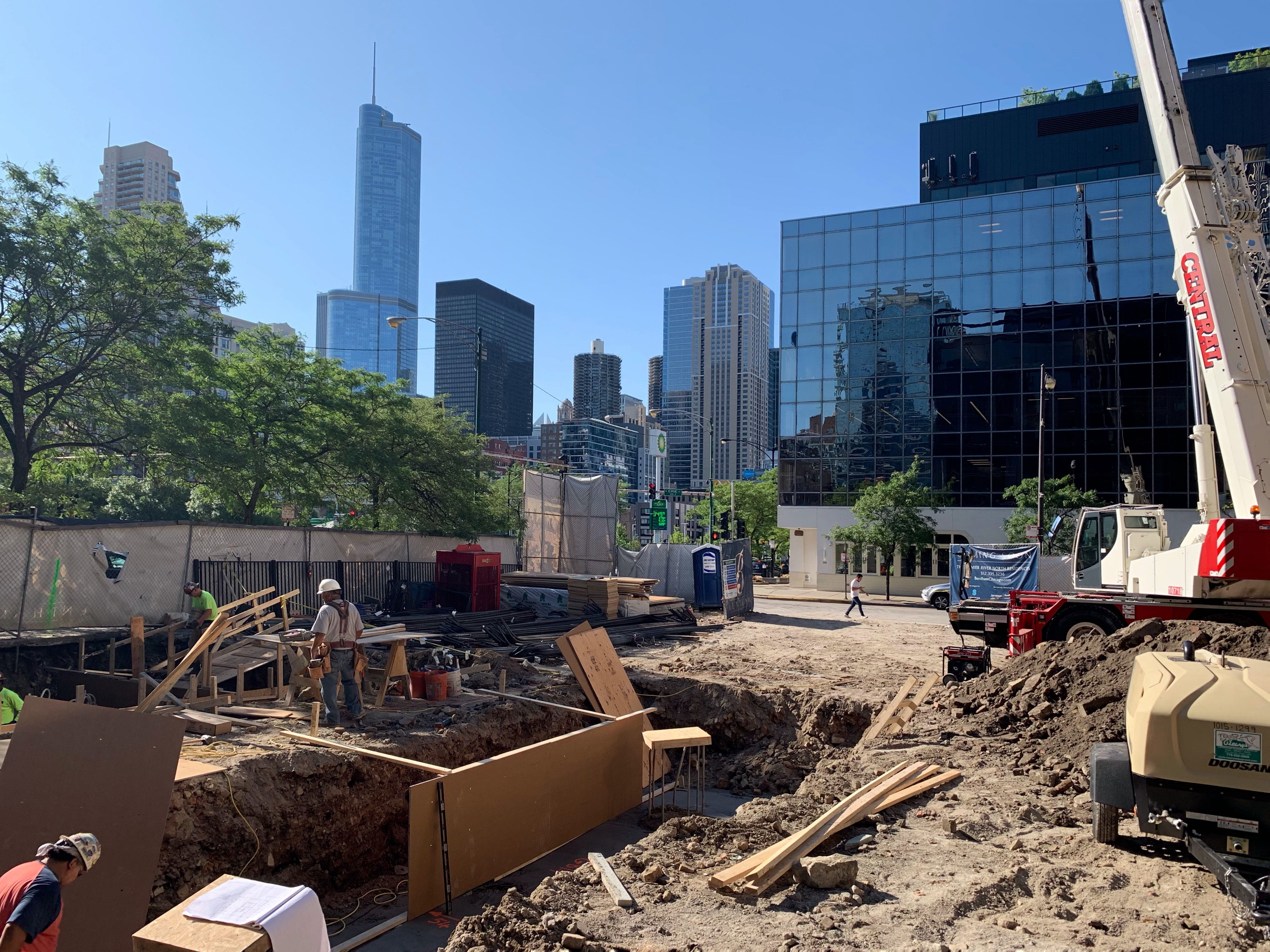 A construction site with workers excavating dirt and building formwork for concrete walls. The site is surrounded by a fence and high-rise towers are visible in the distance.