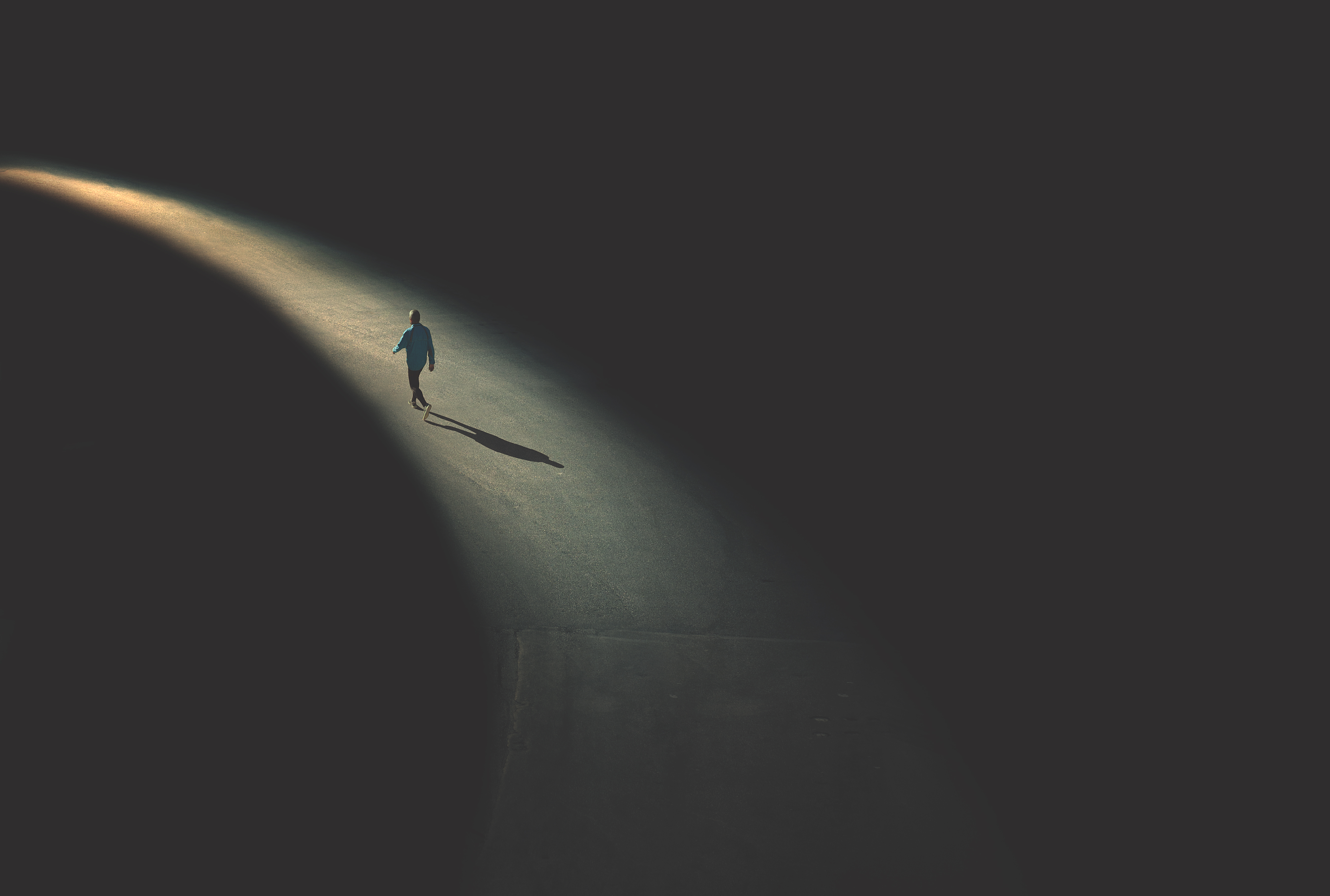 Illustration of single person walking on a path of light against a dark, foreboding background.