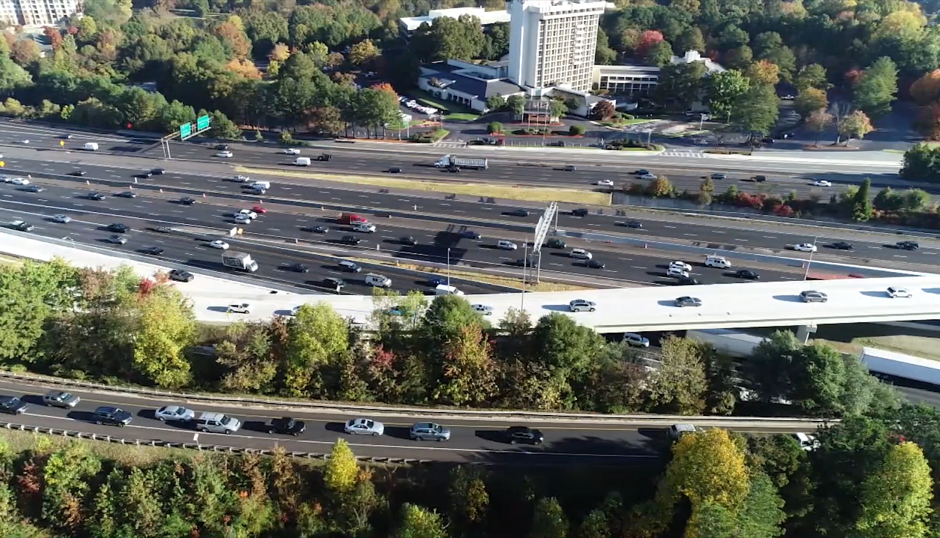 The new express lanes, in white, hop over the general access lanes snuggled between two large clumps of green trees.