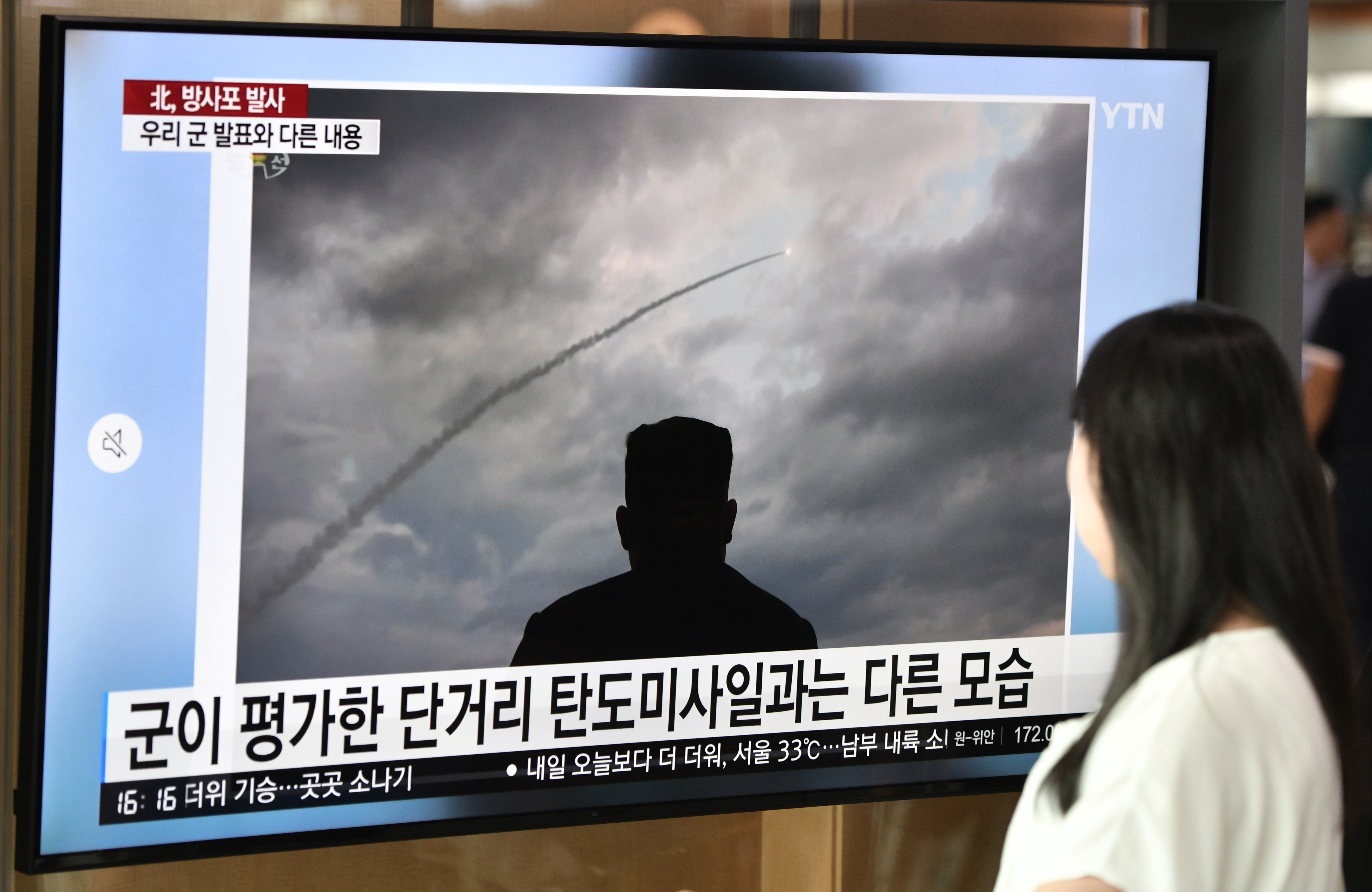 A woman walks past a television news screen showing an image of North Korean leader Kim Jong Un looking at the test-fire of a new multiple rocket launcher, at a railway station in Seoul on August 1, 2019.