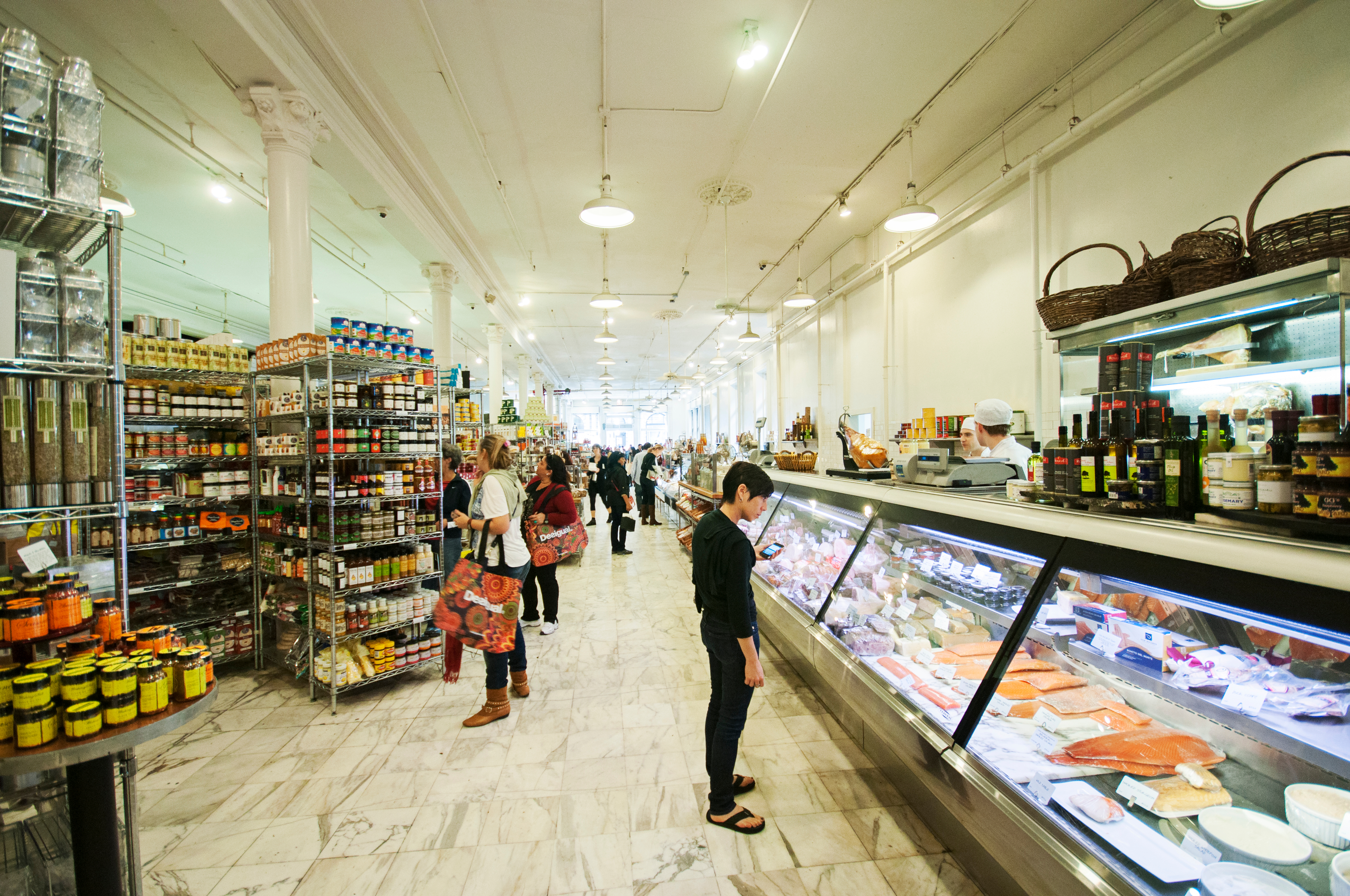 People standing in a grocery aisle, between shelves of condiments and a glass case full of fish.