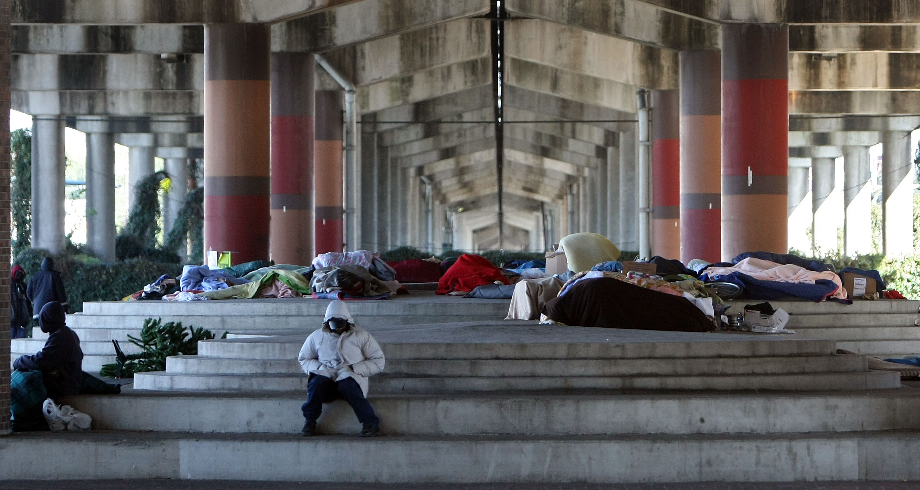 A man in a hooded coat sits on rounded steps under a freeway overpass filled with tents and sleeping bags.