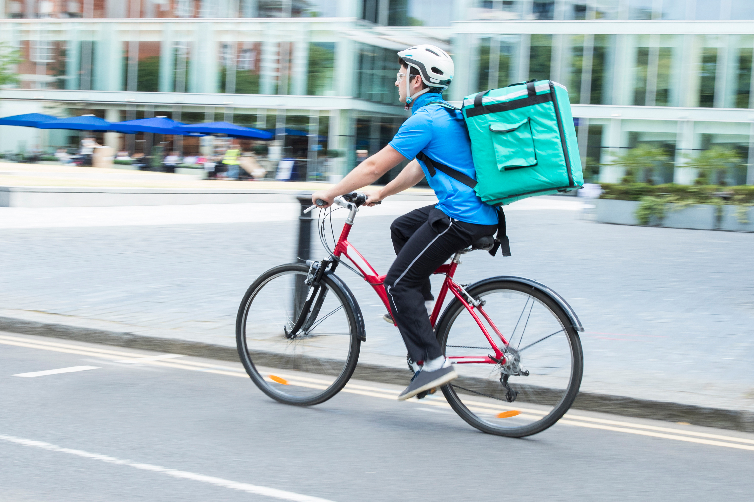 A helmet-wearing delivery person on a bike with a meal warmer strapped to his back.
