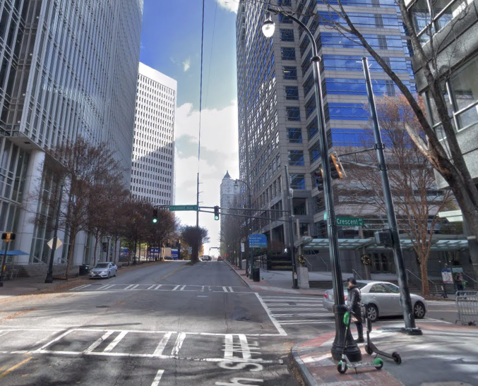 A photo of an atlanta intersection with tall glassy buildings and very few cars.
