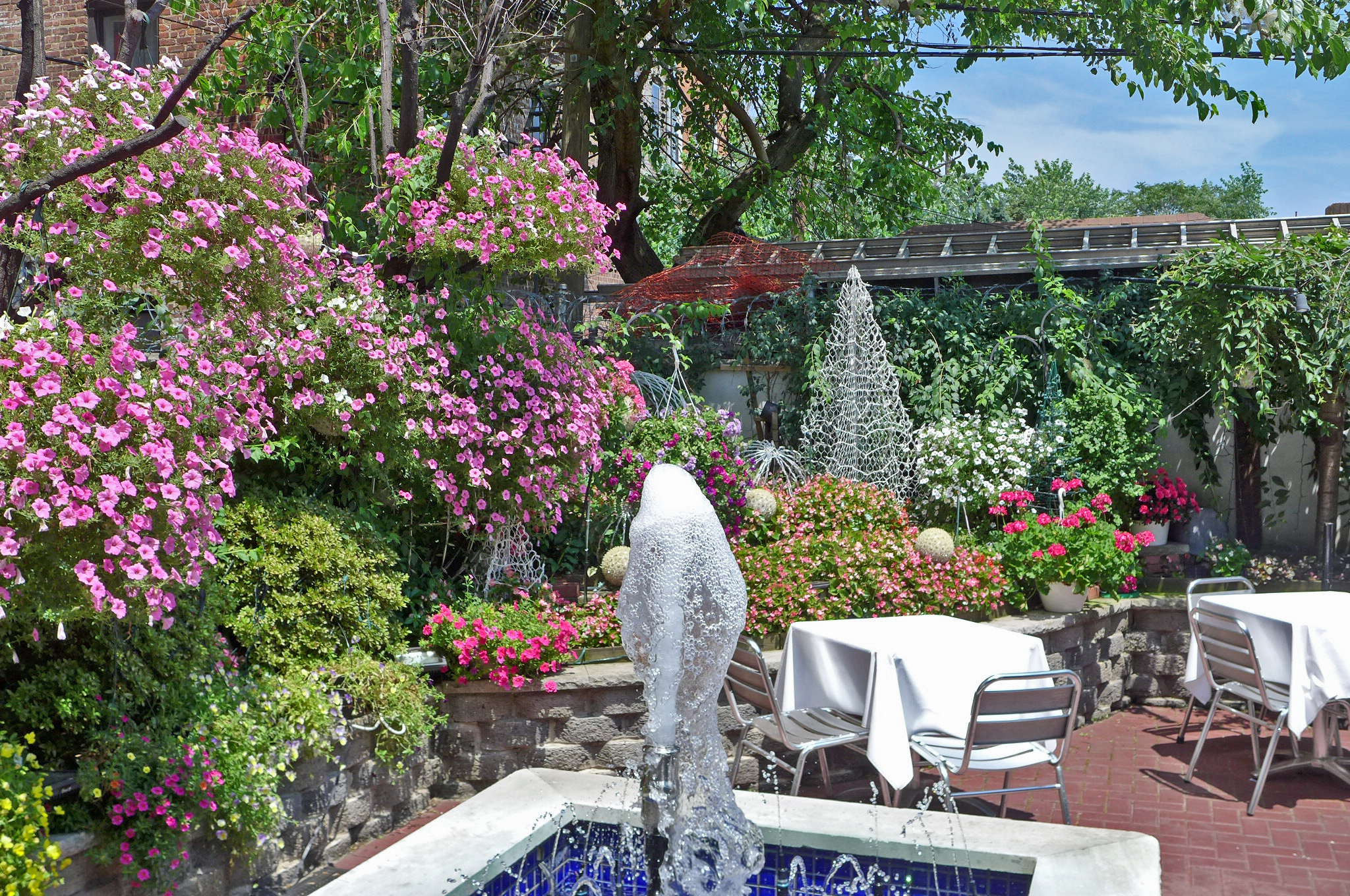 A fountain and flowers fill the back yard dining area.
