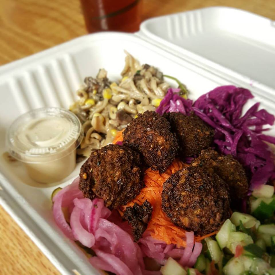 Chickpea fritters sit atop pickled vegetables in a takeout tray