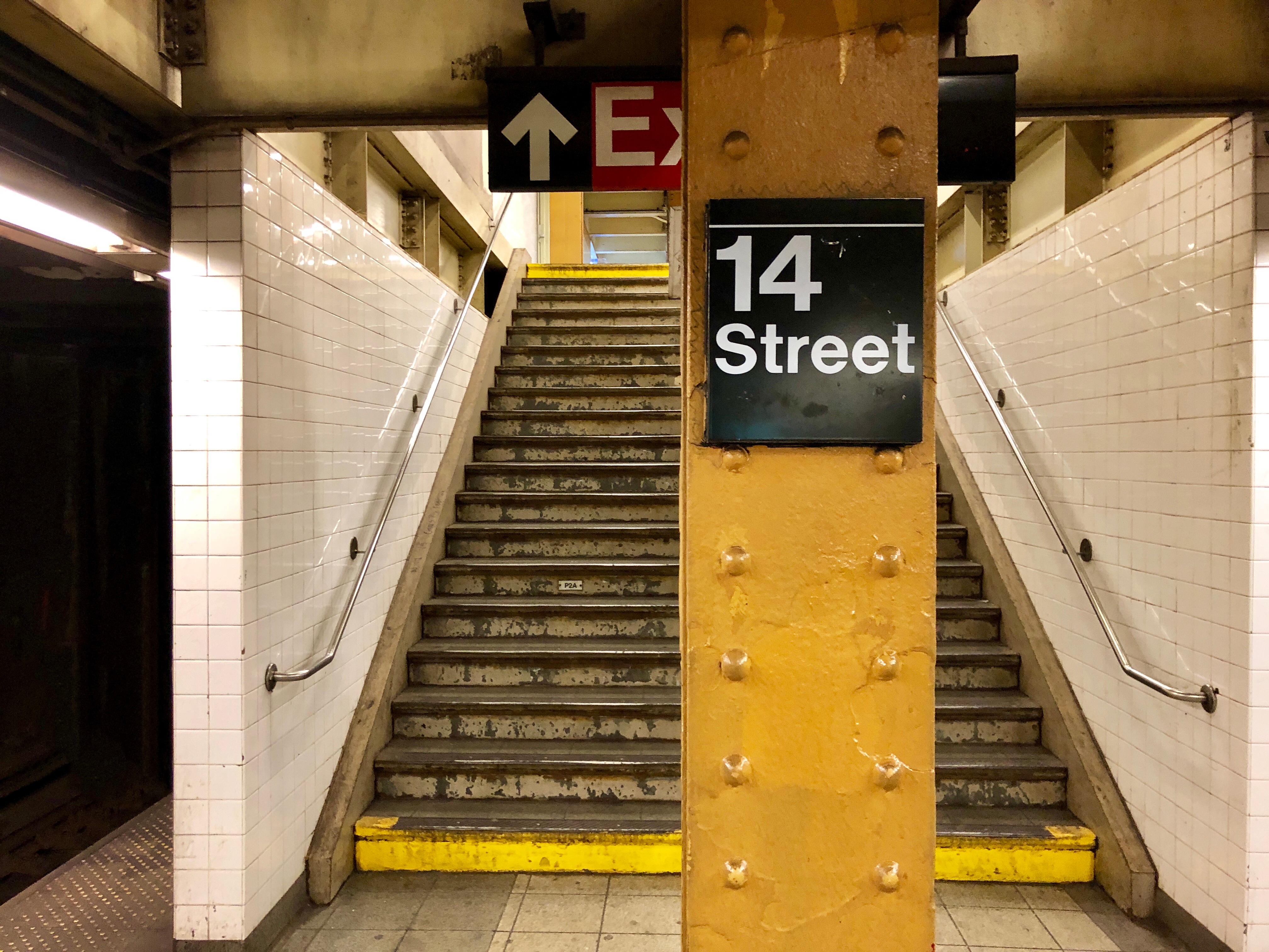 """Stairs are shown behind a column that says """"14 Street"""" in a New York City subway station."""