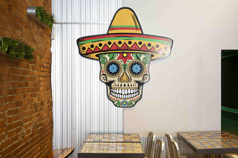 A colorful skull with a sombrero decorates a wall at Taqueria el Barrio near Boston University