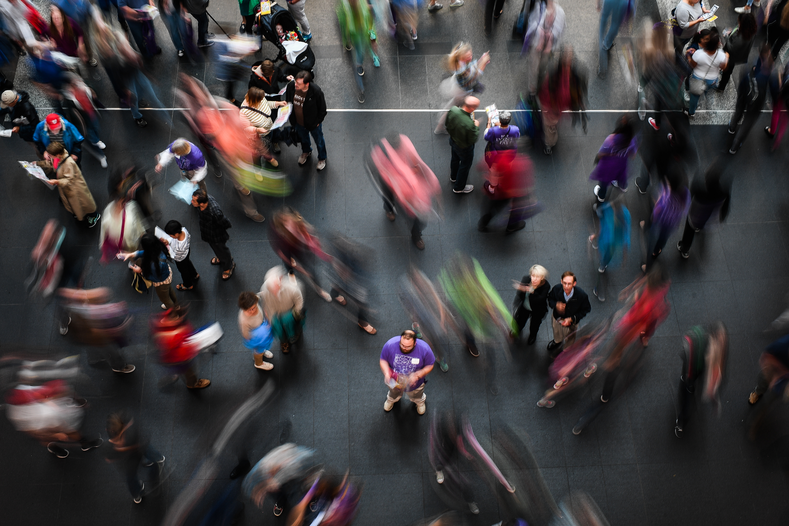 About two dozen people mill about the Walter E. Washington Convention Center at the 2017 National Book Festival. The photos captures some of them in motion.