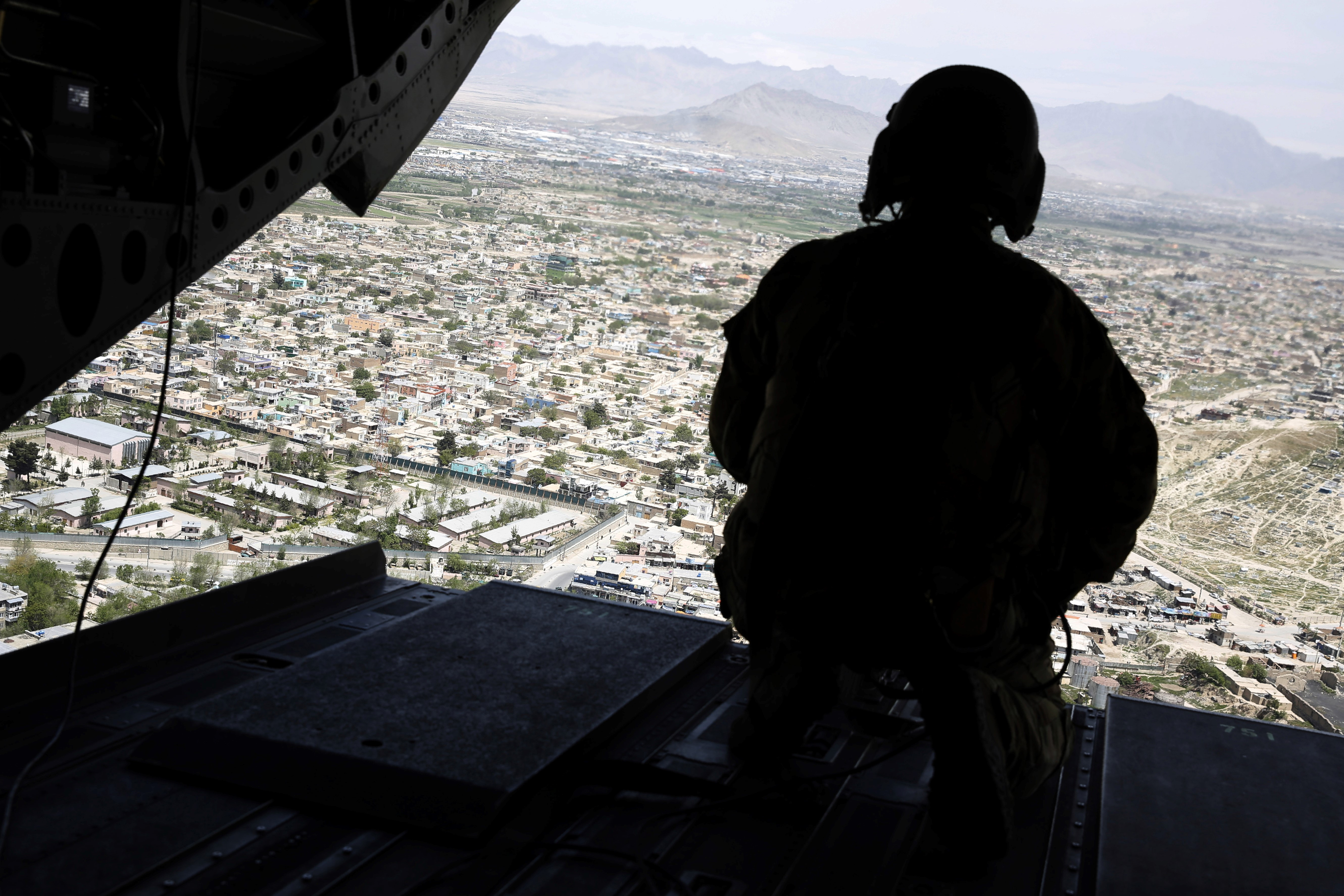 A US soldier mans a weapon at the tailgate aboard the helicopter carrying former Defense Secretary James Mattis in the Afghan capital Kabul on April 24, 2017.