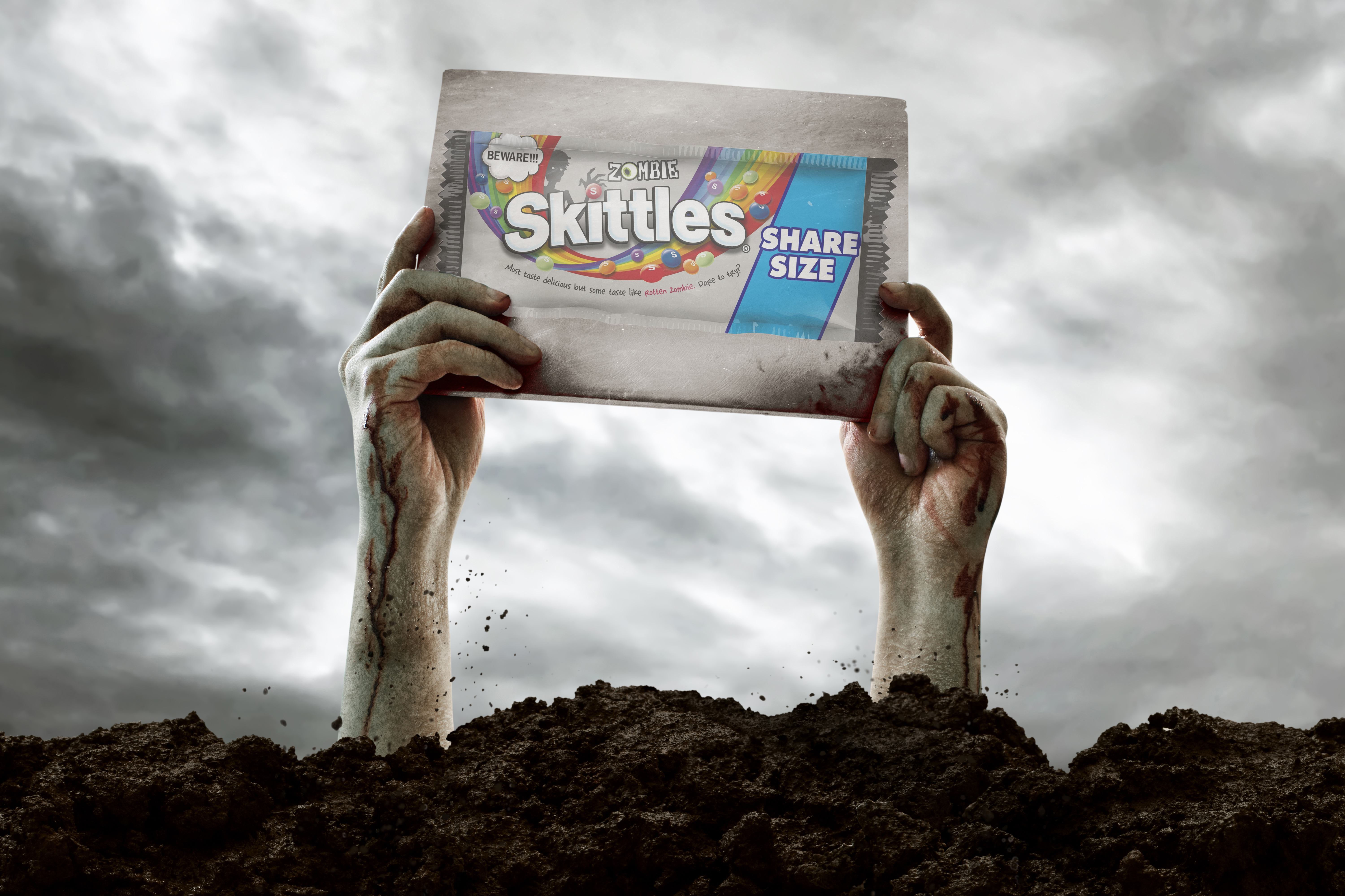 A pair of zombie hands sticking out of the dirt, holding up a sign with an image of Zombie Skittles.