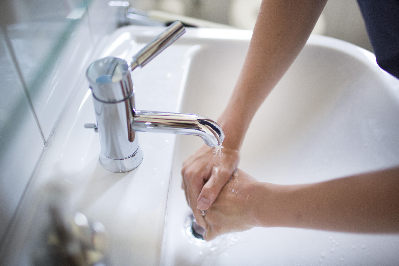 Man washes hands in sink