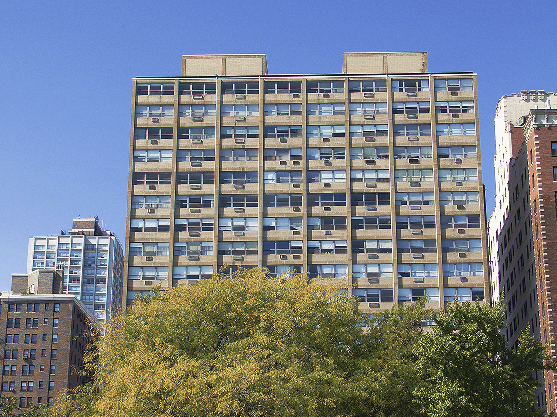 A street level view of a 22-story apartment tower rising above a tree canopy. The building has a rectangular row of windows framed by beige brick and concrete. It is surrounded by other buildings under a blue cloudless sky.