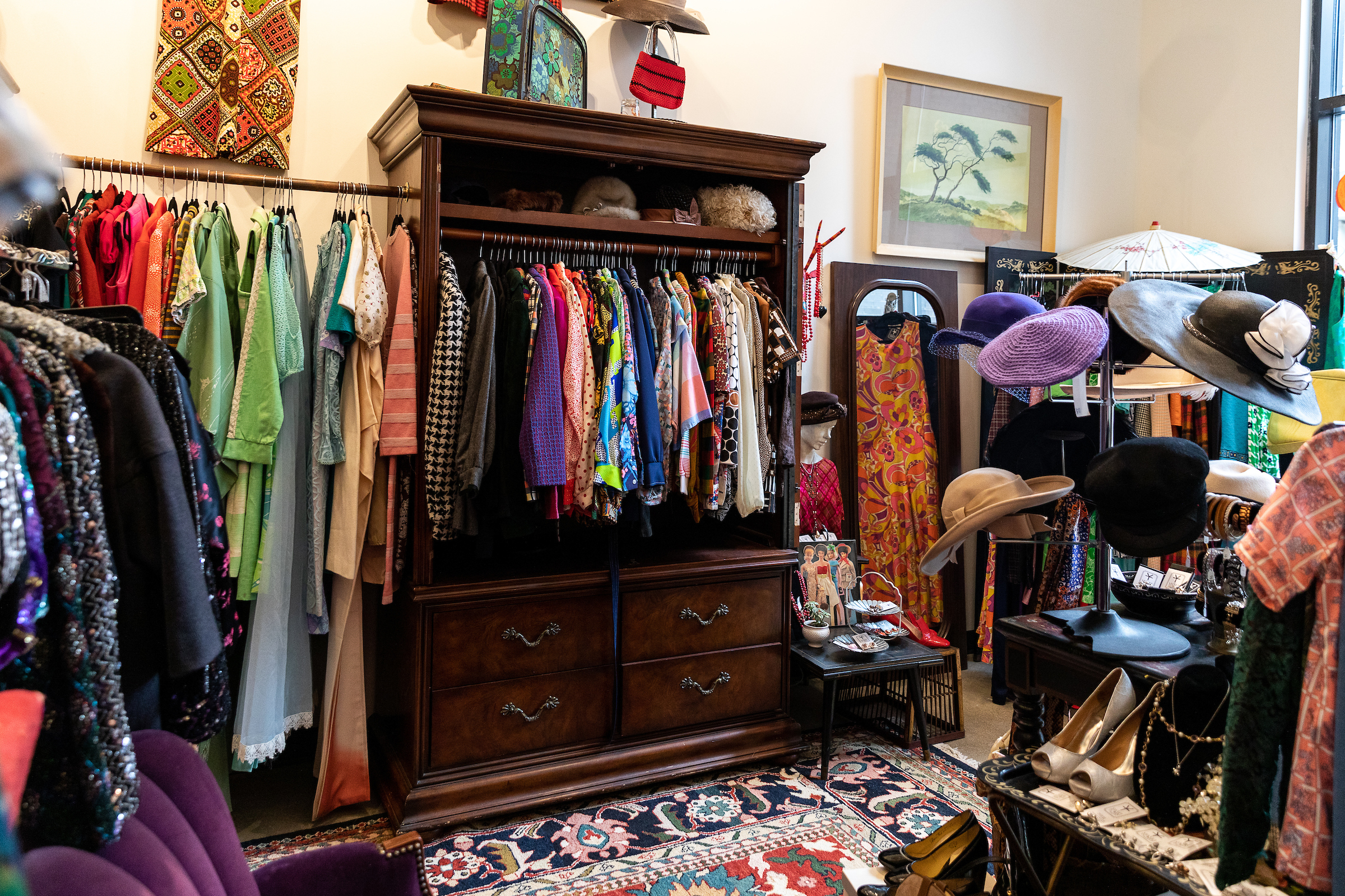Colorful dresses and hats on racks at a vintage clothing shop downtown