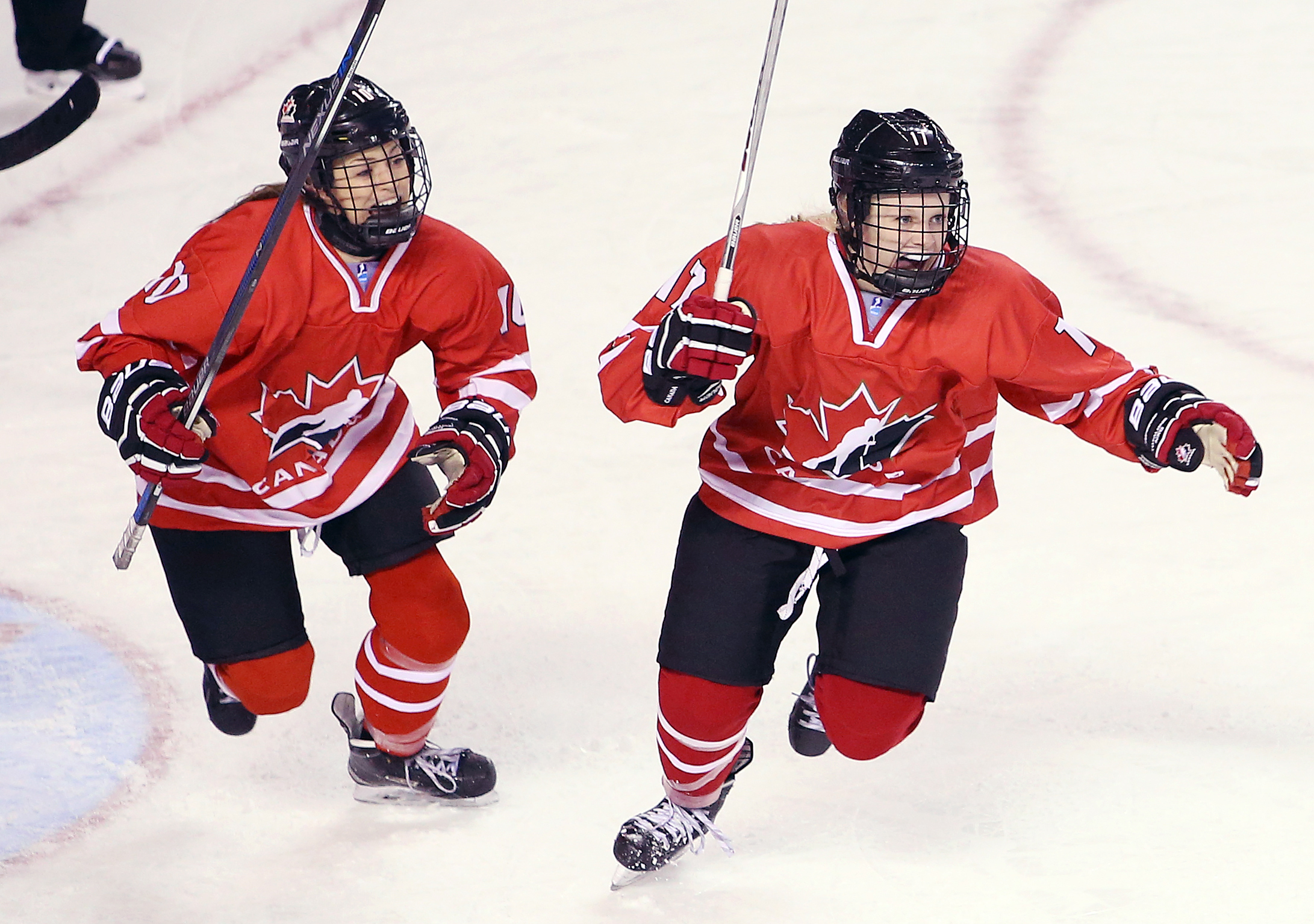 Kristin O'Neill #10 and Emma Maltais #17 of Team Canada celebrate a goal by teammate Ashton Bell #26 in a semifinal game against Team Russia during the 2016 IIHF U18 Women's World Championships