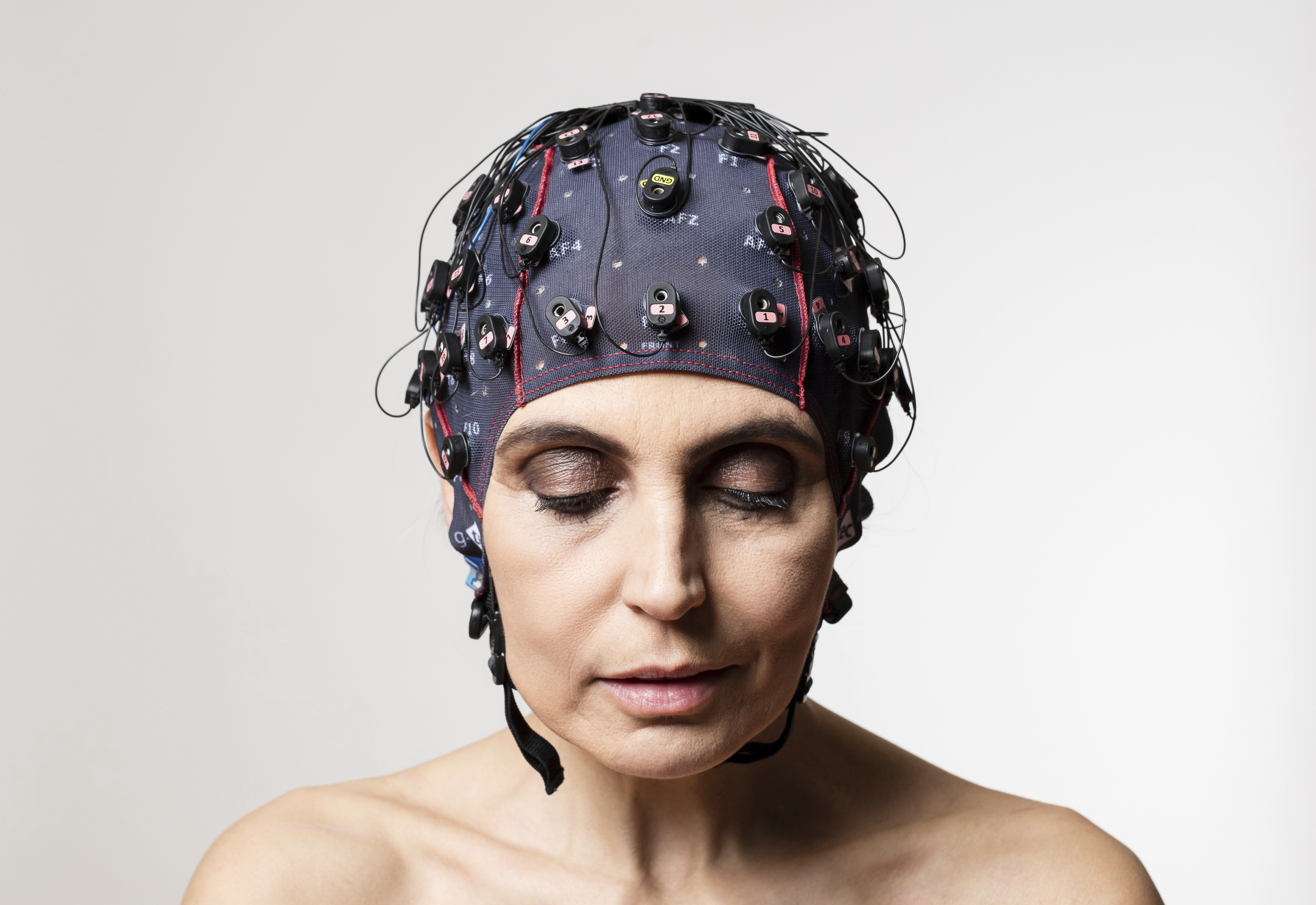 A woman equipped with a brain-computer interface that she is wearing as a bathing-suit-style cap on her head.