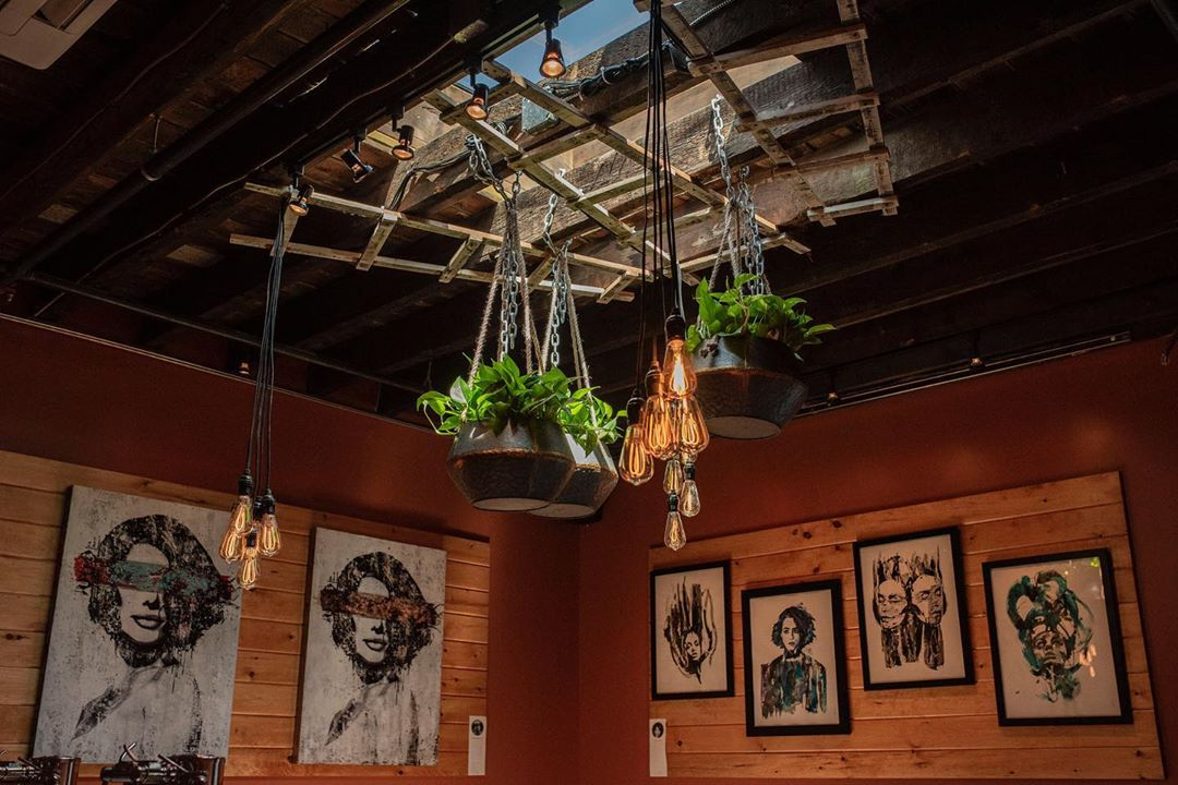Art hangs on the wooden walls and plants hang from the ceiling near a skylight, along with bare lightbulbs and old ladders, at Create Gallery & Cocktail Lounge at Bow Market in Somerville's Union Square