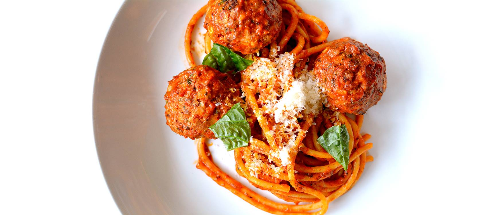 A white bowl of spaghetti and three meatballs topped with parmesan and fresh basil