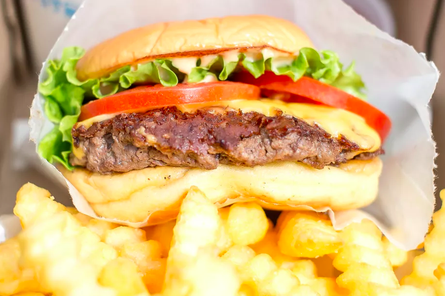 Close up of a Shake Shack burger topped with cheese, lettuce, and tomato, with crinkle-cut french fries