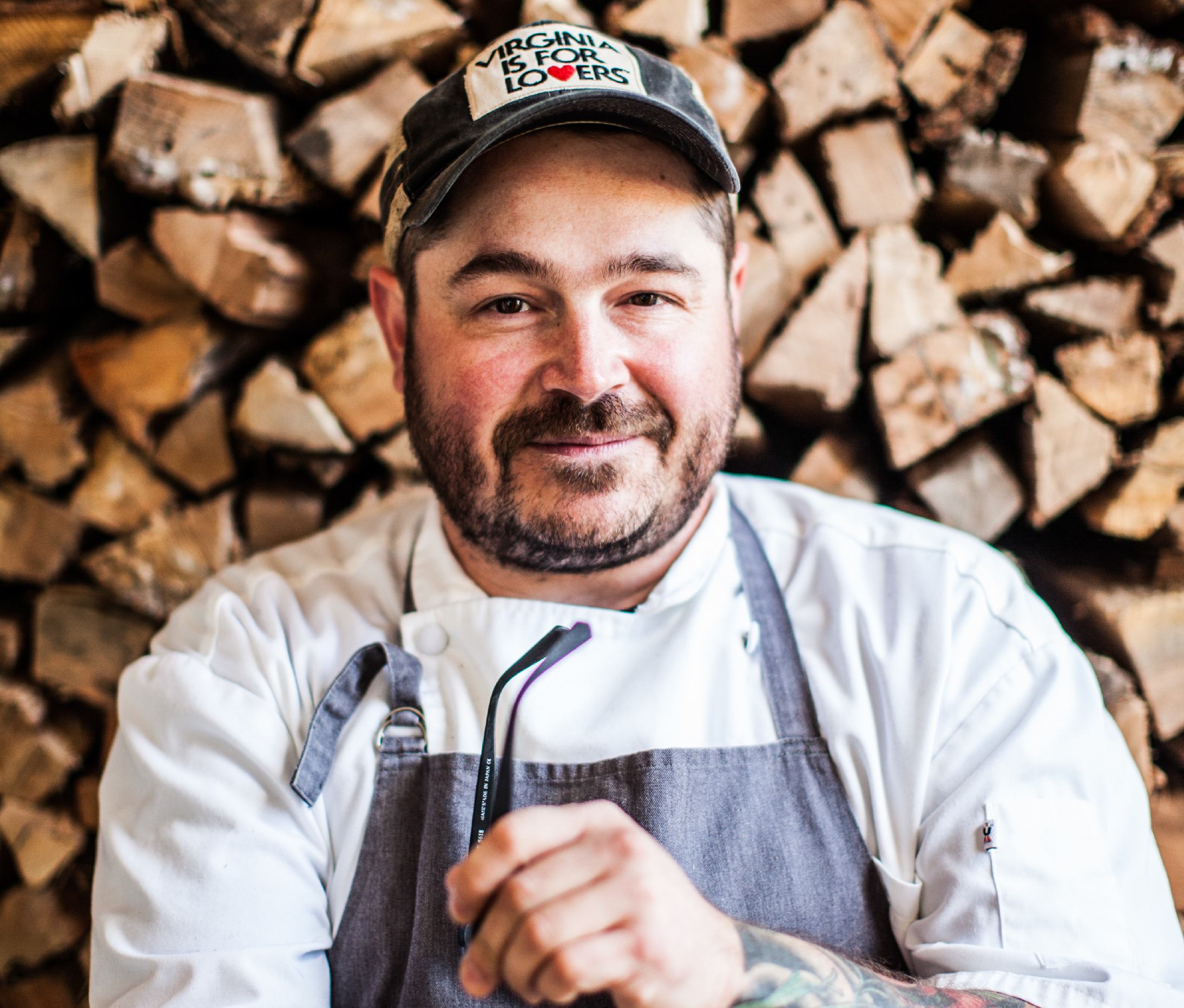 Sean Brock holding glasses in apron, wood pile behind