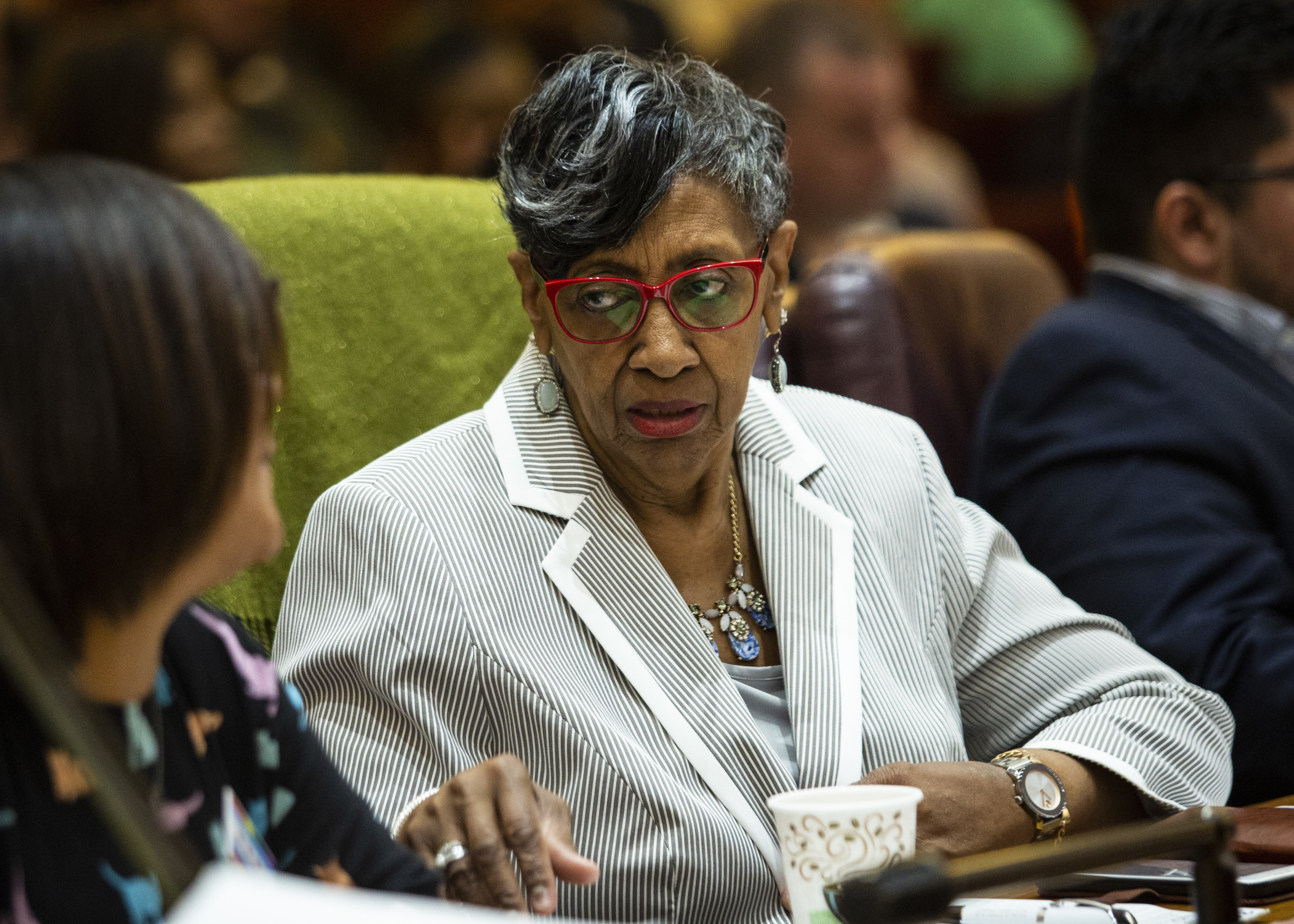 Ald. Carrie Austin (34th) talks to a colleague at the Council meeting Jun 12, two weeks after her South Side ward office was raided by the feds.