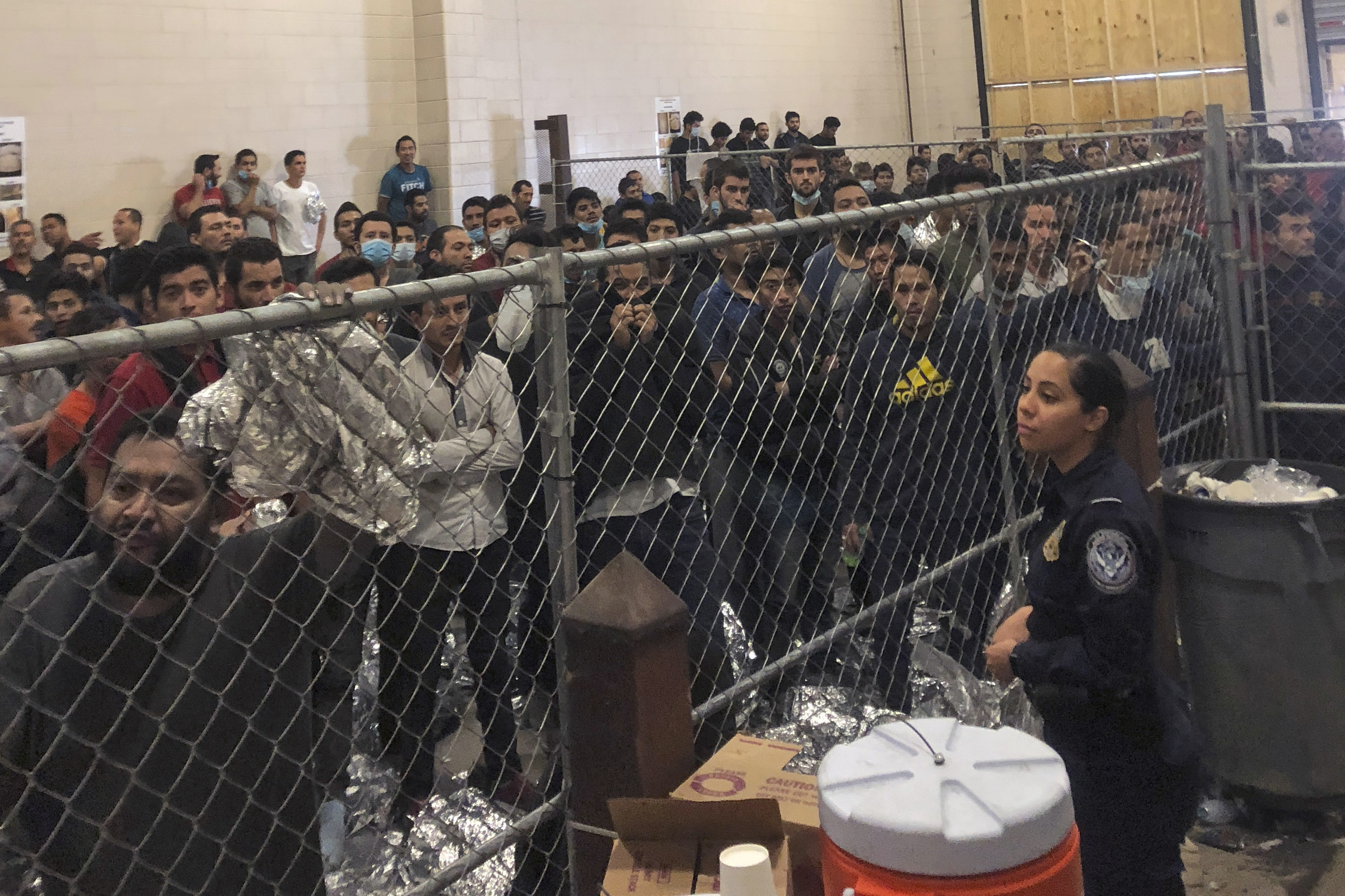 In this July 12, 2019 file photo, men stand in a U.S. Immigration and Border Enforcement detention center in McAllen, Texas, during a visit by Vice President Mike Pence. Immigration lawyers say a pattern has repeated itself for several weeks in migrant de