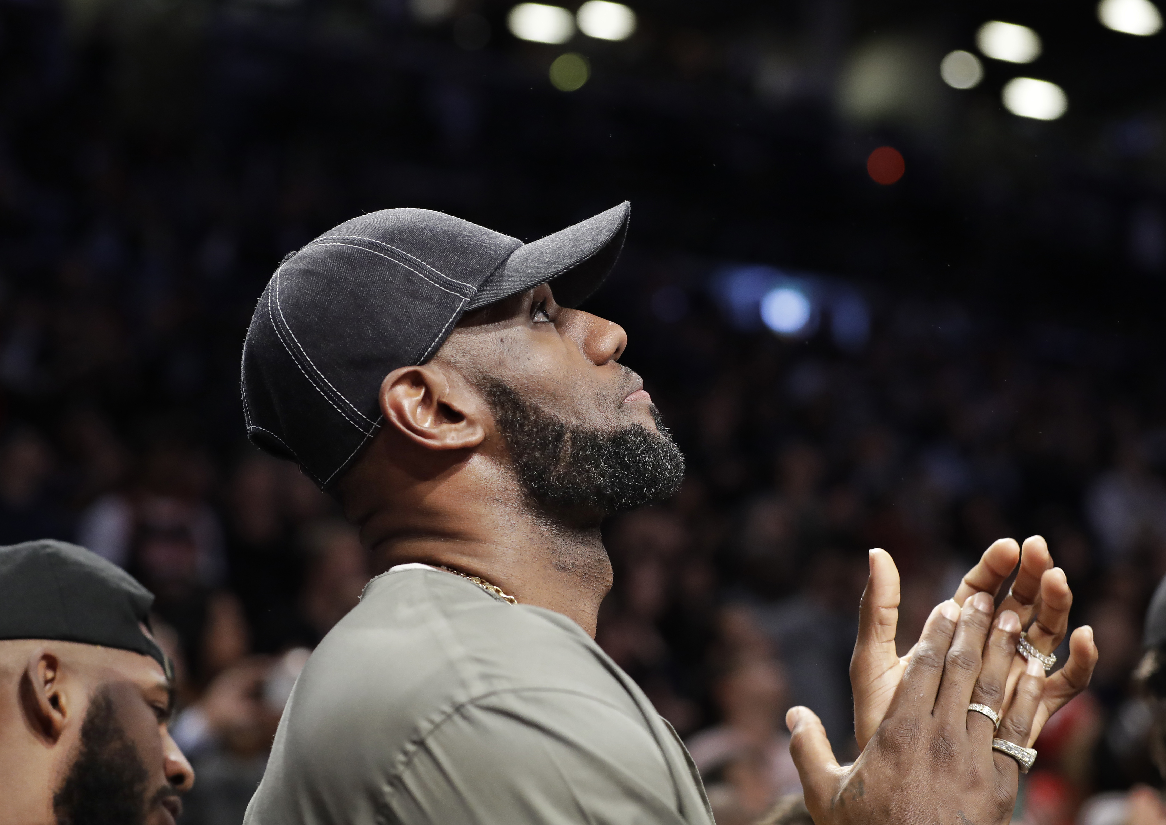 LeBron James applauds as he watches on a giant overhead video screen as a member of the military is honored during a timeout in the first half of an NBA game between the Brooklyn Nets and the Miami Heat, Wednesday, April 10, 2019, in New York. James and o