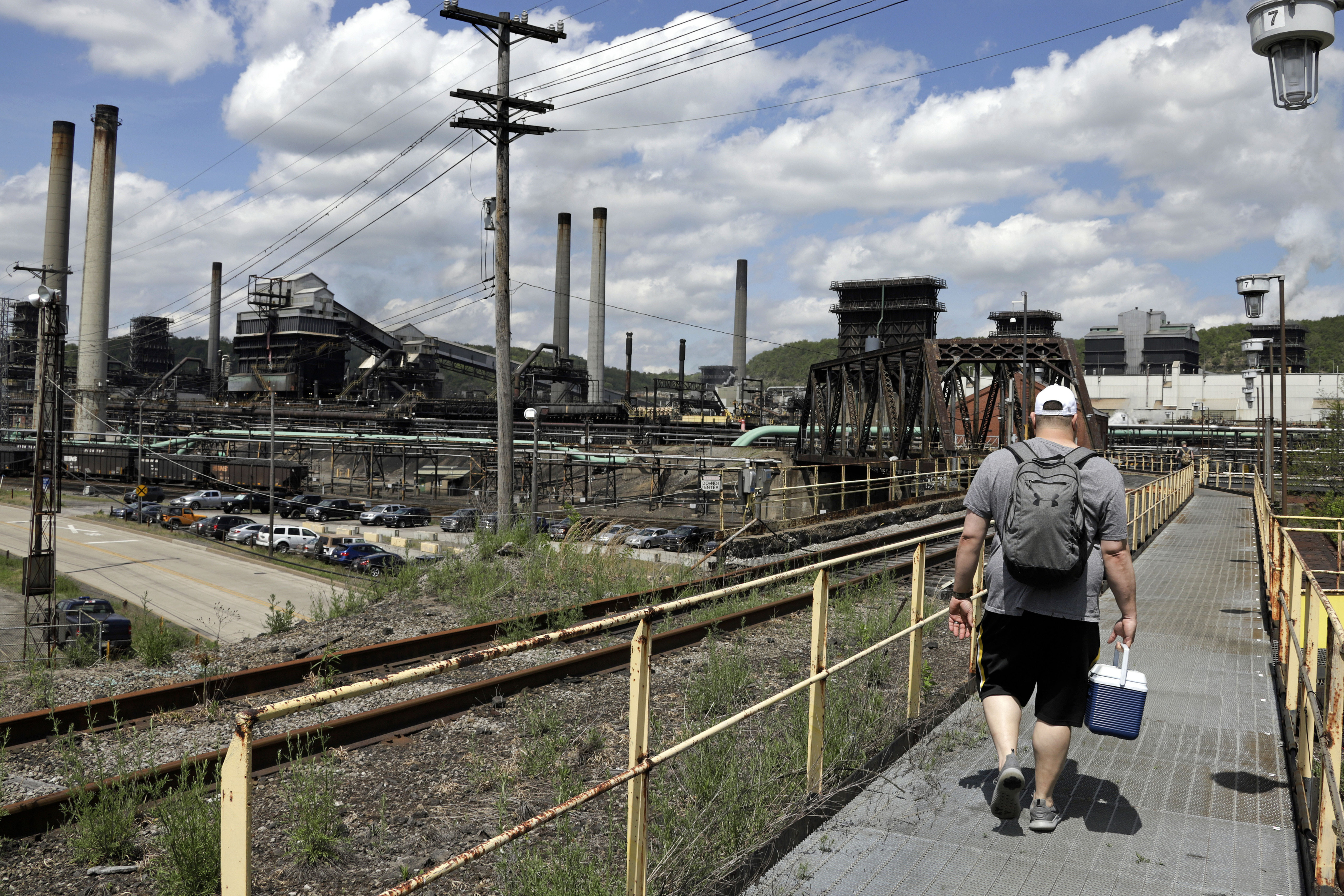 FILE - In this May 2, 2019, file photo a worker arrives for his shift at the U.S. Steel Clairton Coke Works in Clairton, Pa. Two government reports last week, on economic growth during the April-June quarter and orders for durable manufactured goods, conf