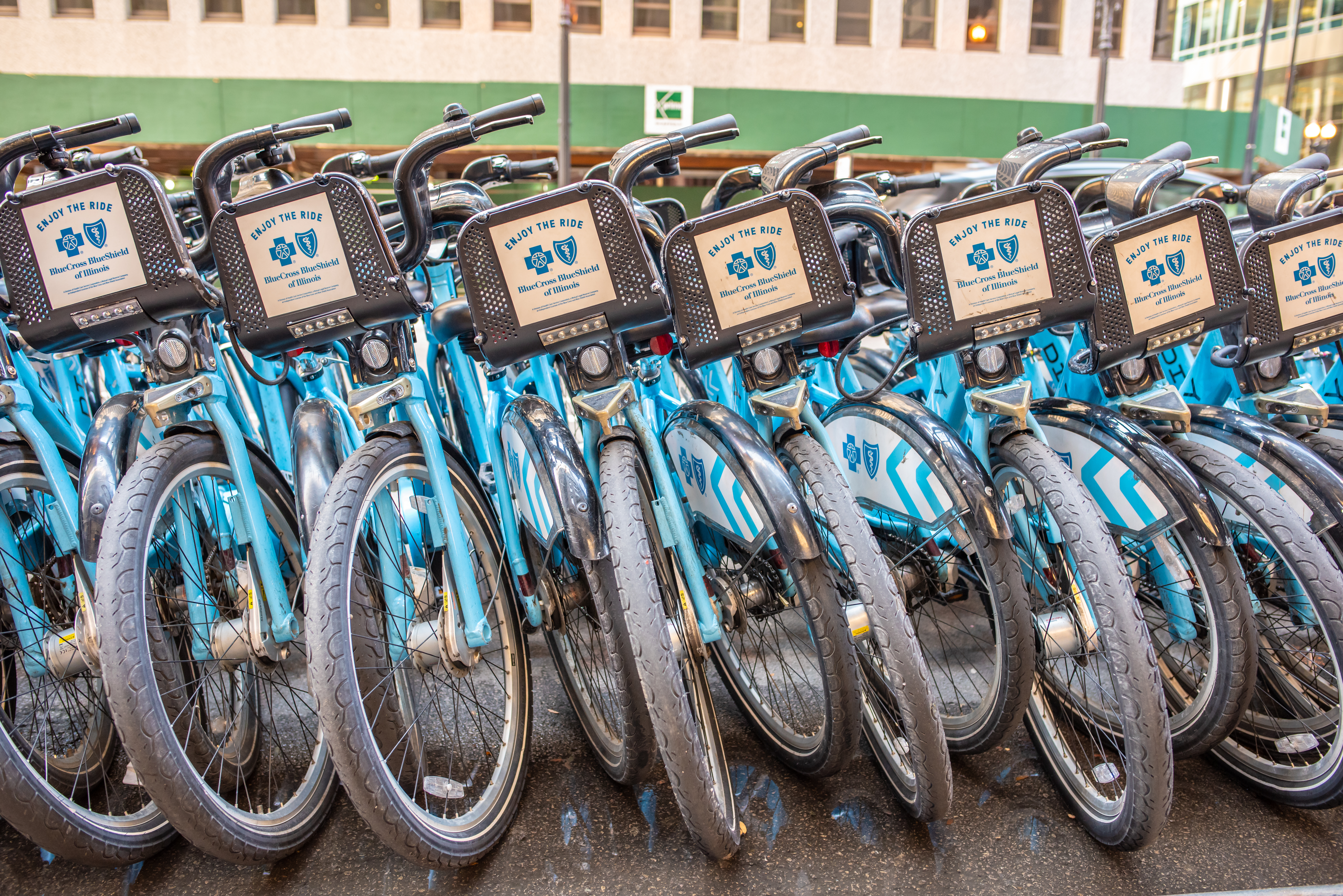 A front view of seven blue Divvy bikes with black mesh baskets and dirty tires.