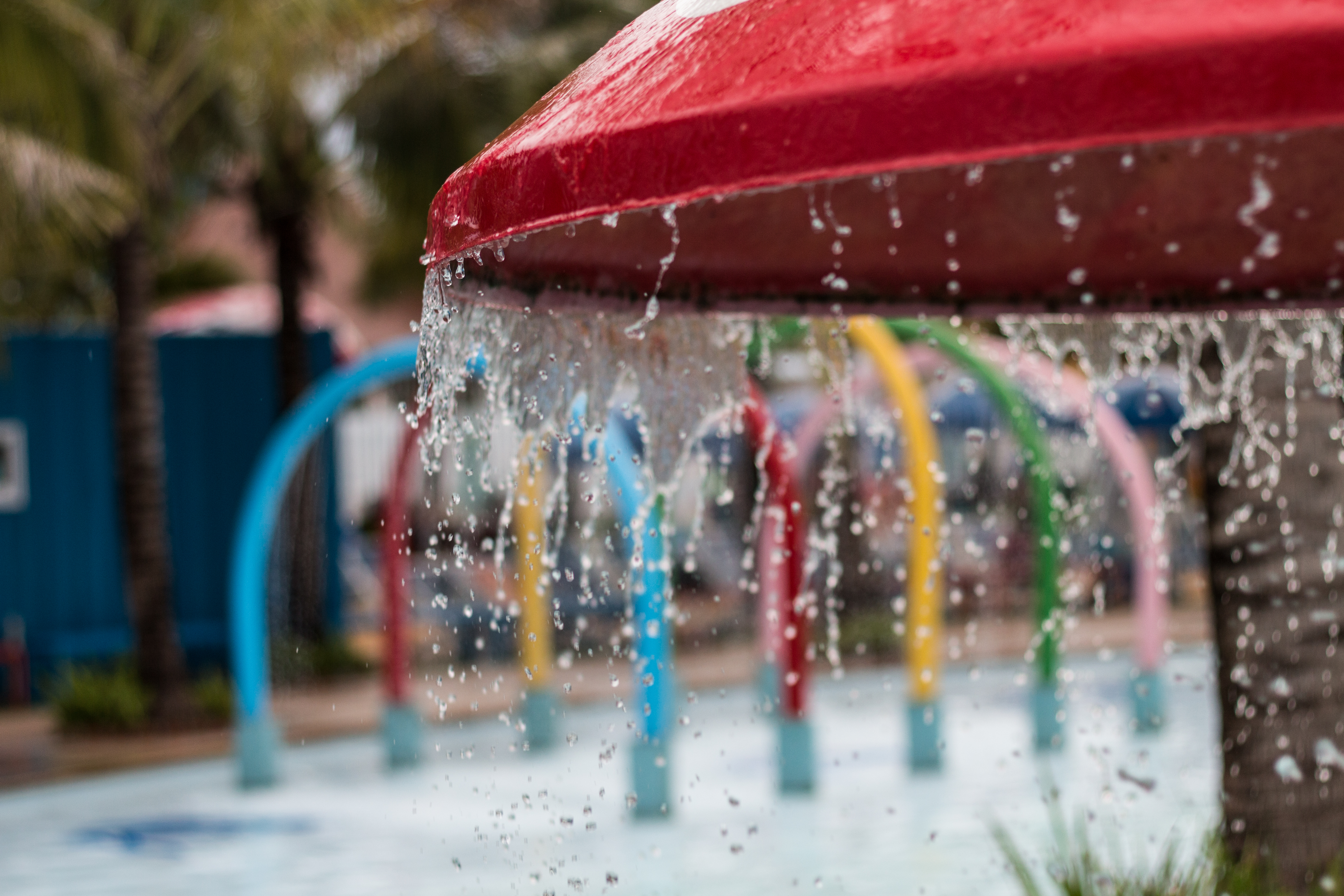 A red mushroom-shaped structure dips water at a spray park, with multicolor sprinklers in the background.