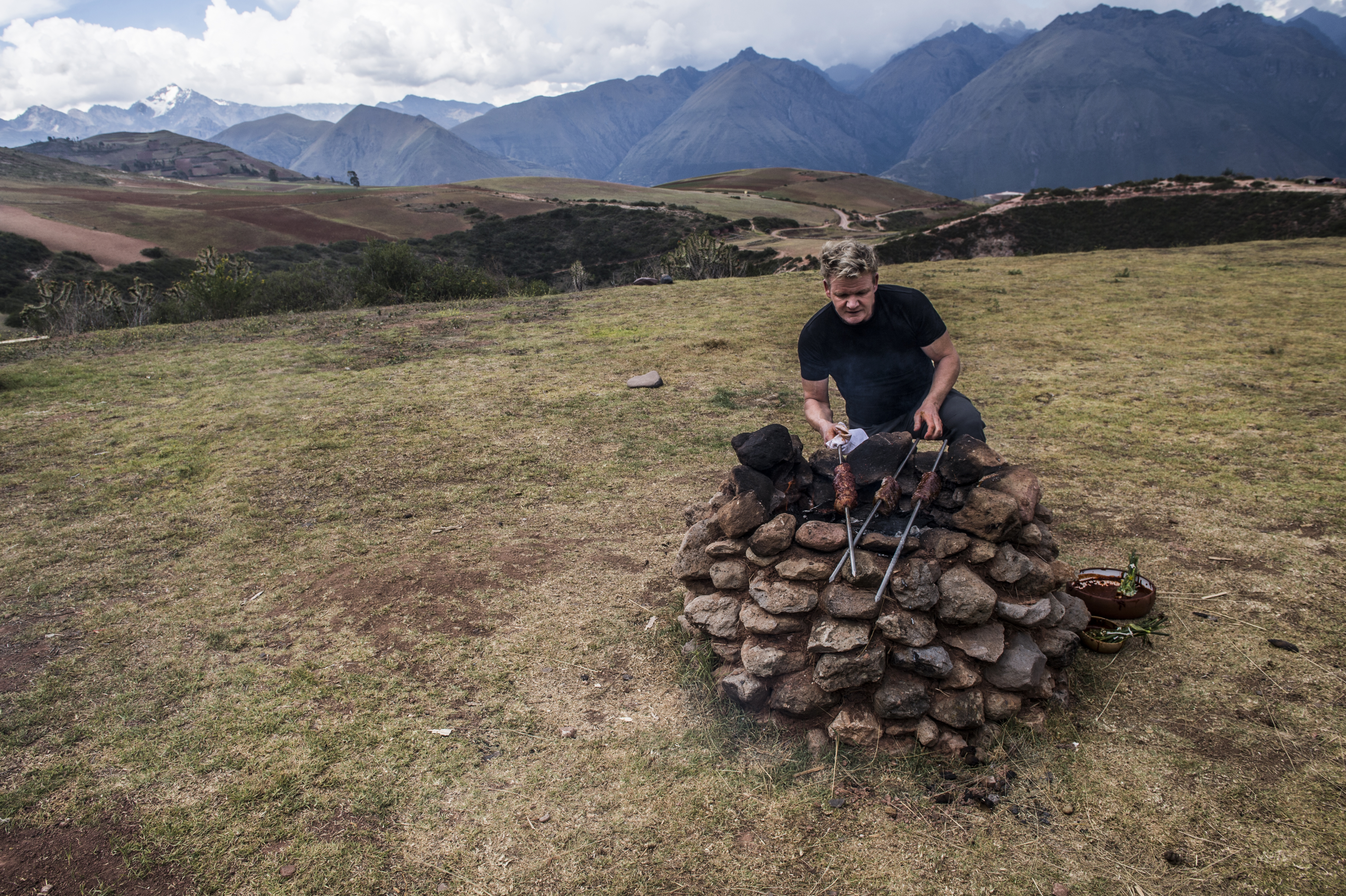 """Chef Gordon Ramsay cooks on an outdoor stove of hot rocks in Peru's Sacred Valley, in an episode of his new travel/culinary series """"Uncharted."""
