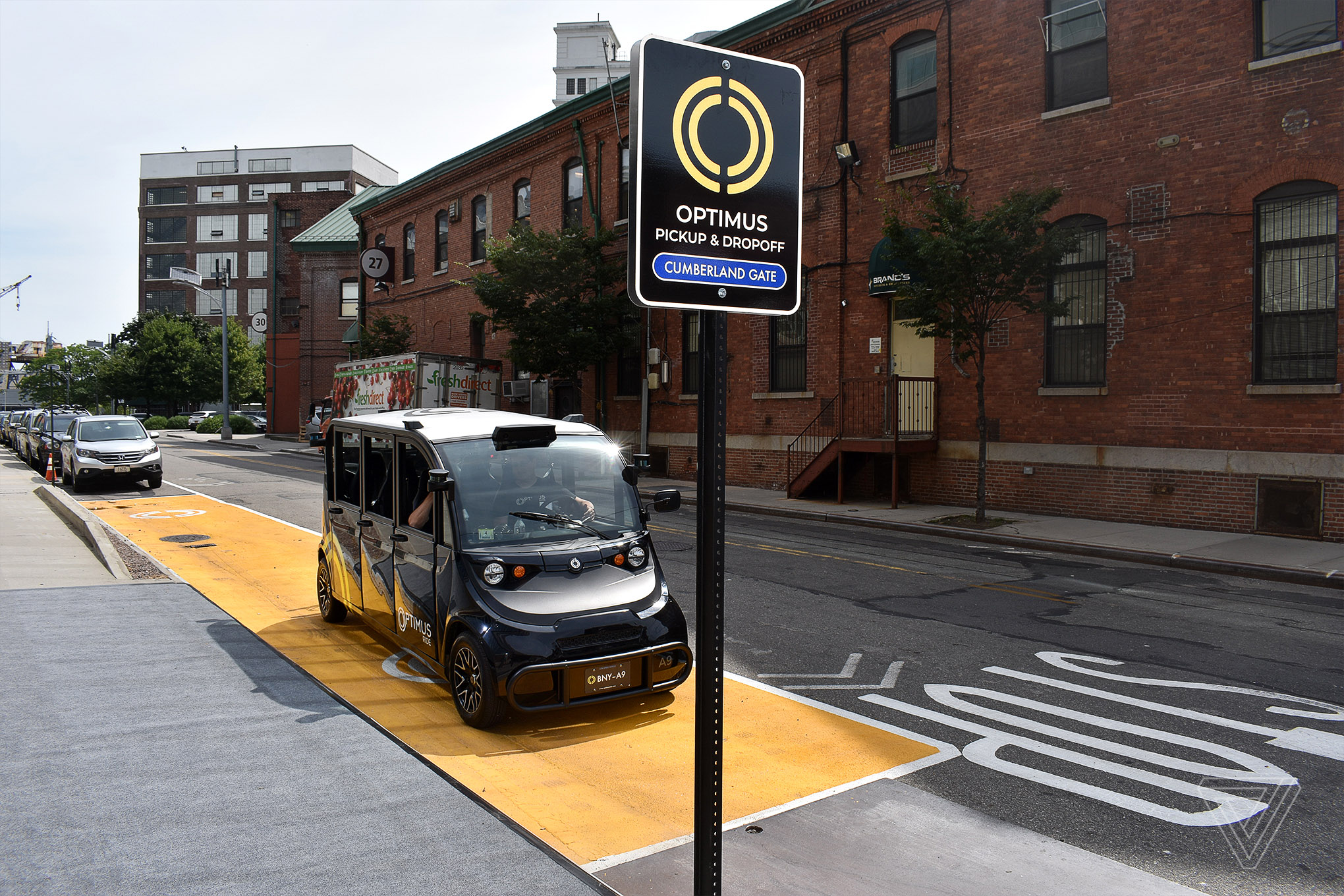 """A black self-driving car is parked on a New York City street behind a sign that reads """"Optimus Pick-Up and Drop-Off: Cumberland Gate."""""""