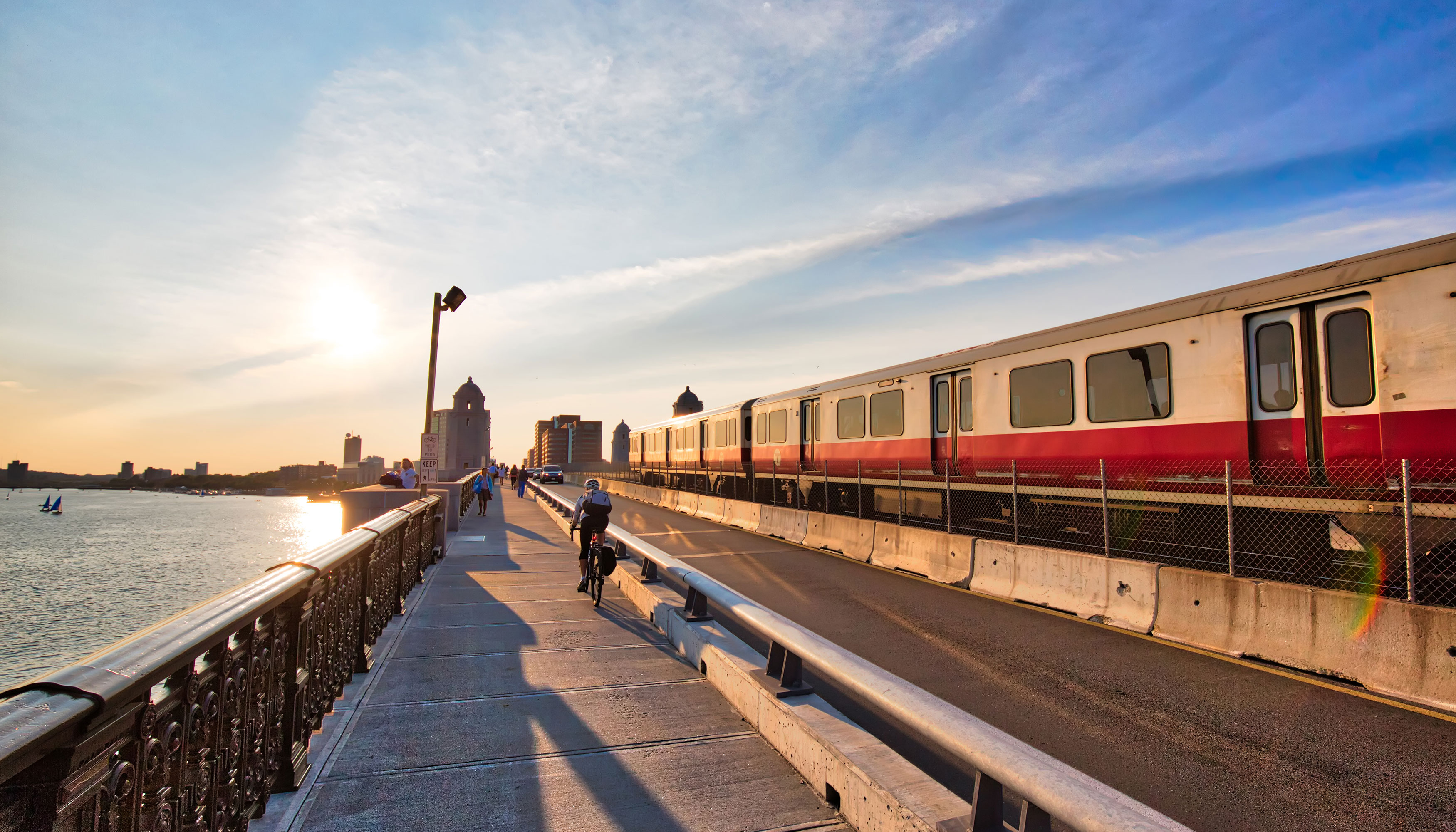 Boston train rides on a track with a view of a river on the left side along with a sunset.